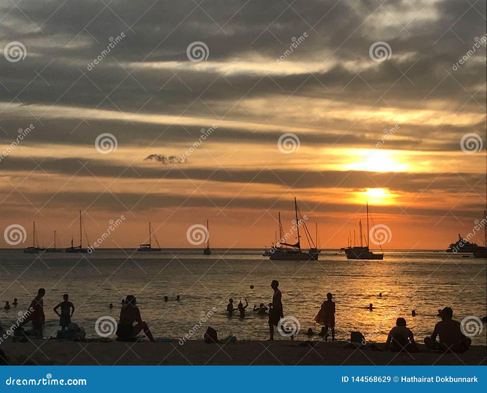Sch?ner Himmel und Ozeanstrand wenn Sonnenuntergang und Leute auf dem Strand
