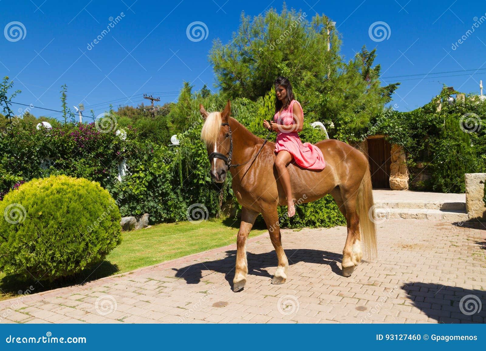 Schöner junger Brunette mit rotem Kleid und ihren braun-blonden hors