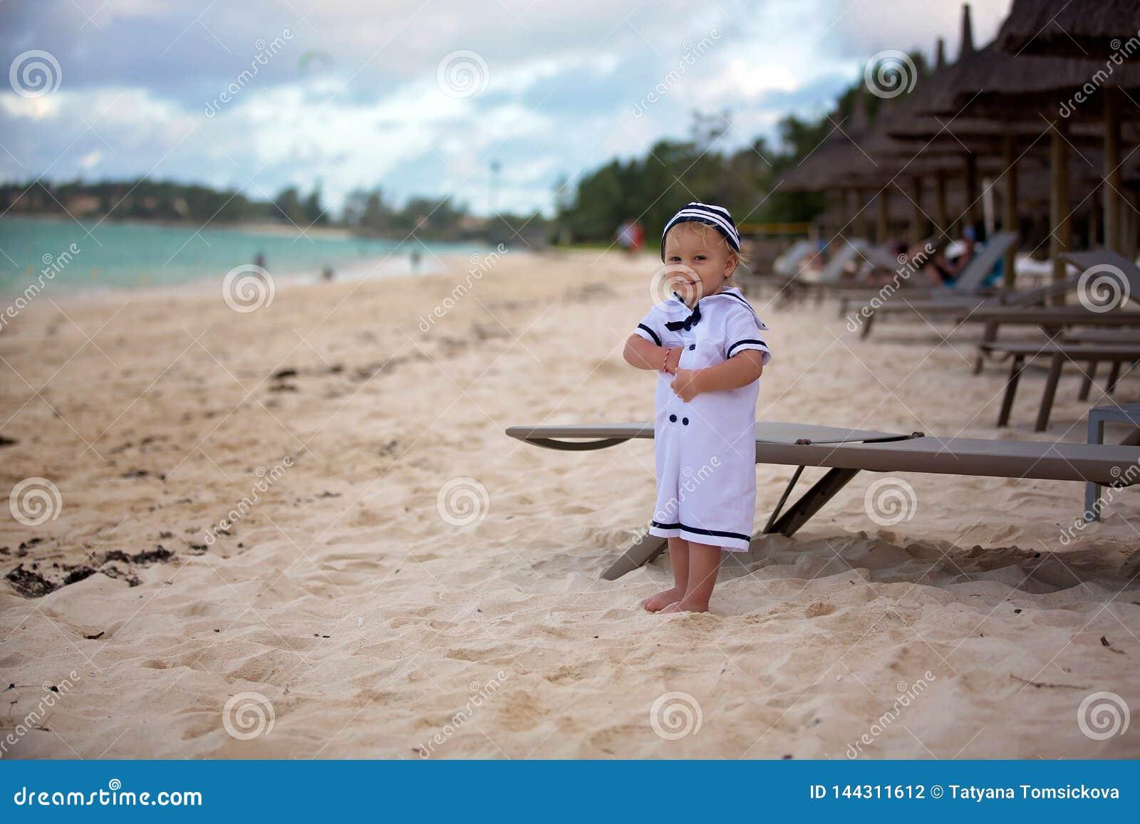 Schöner Kleinkindjunge, gekleidet als Seemann, spielend auf dem Strand auf dem Sonnenuntergang und genießen tropische magische Fe