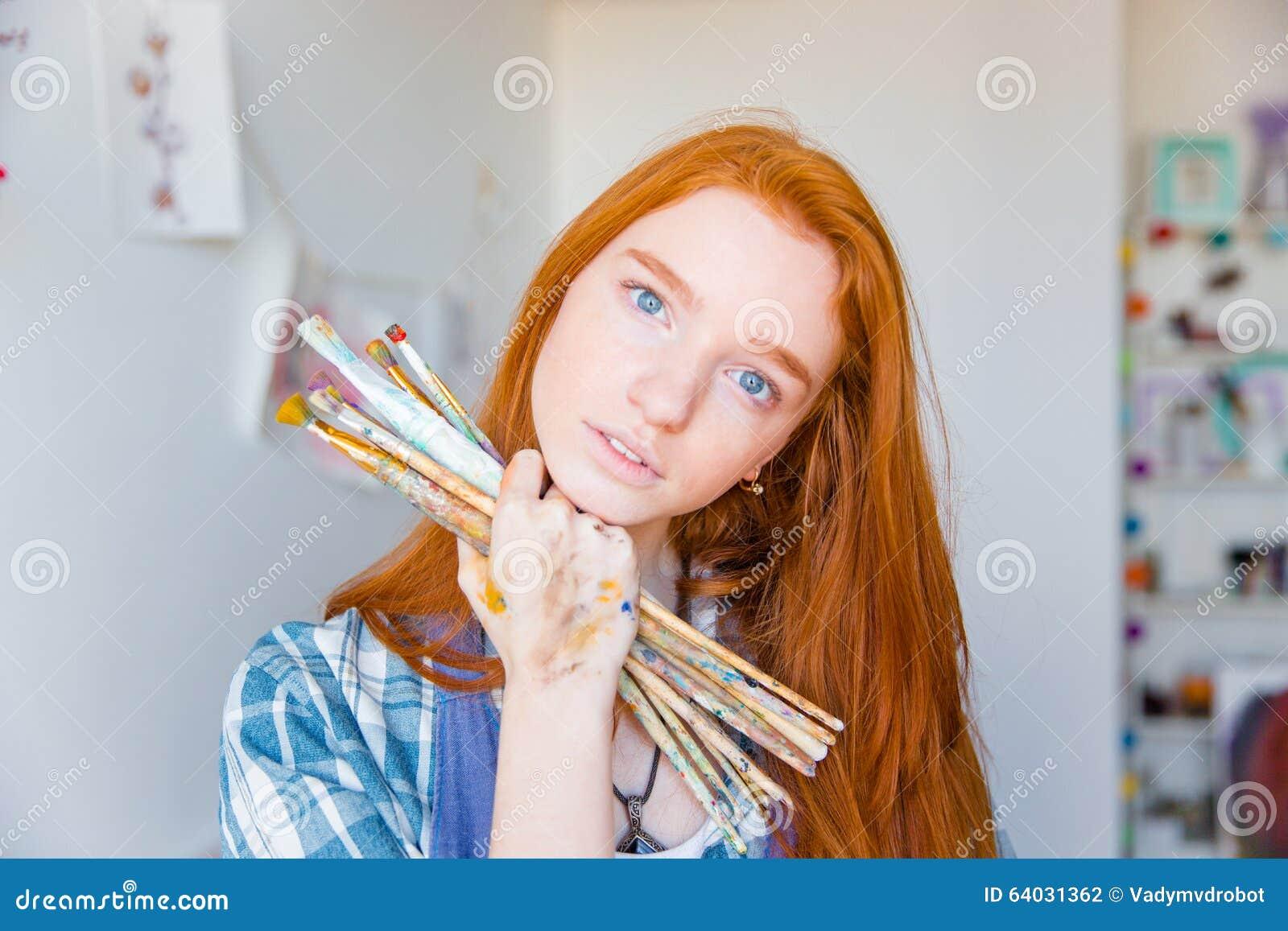 Schöner nachdenklicher Maler der jungen Frau, der Malerpinsel im Kunststudio hält