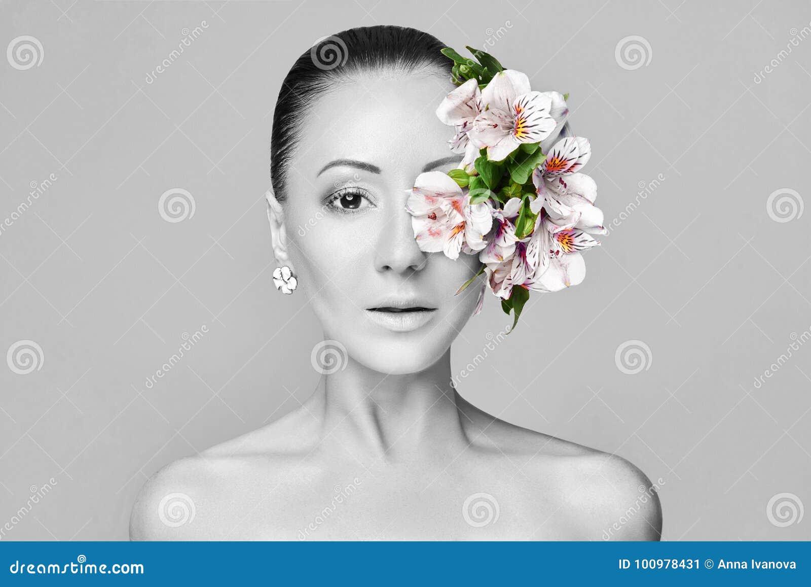 Schöner nackter asiatischer attraktiver Brunette mit Blumen auf seinem hea