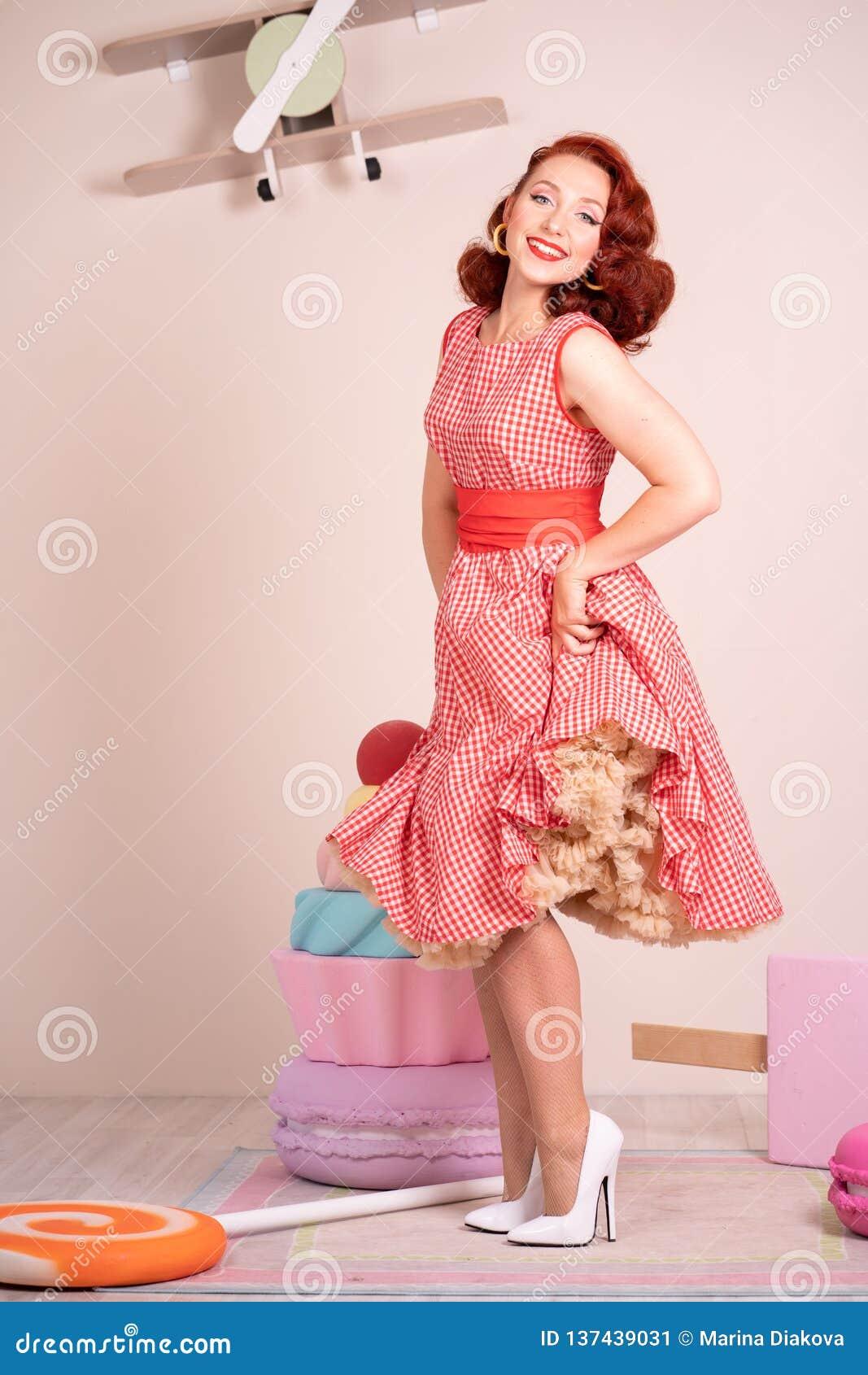 Schöner rothaariger Pinup, der glücklich Mädchen aufwirft in einem Retro- roten Kleid und in weißen hohen Absätzen lächelt