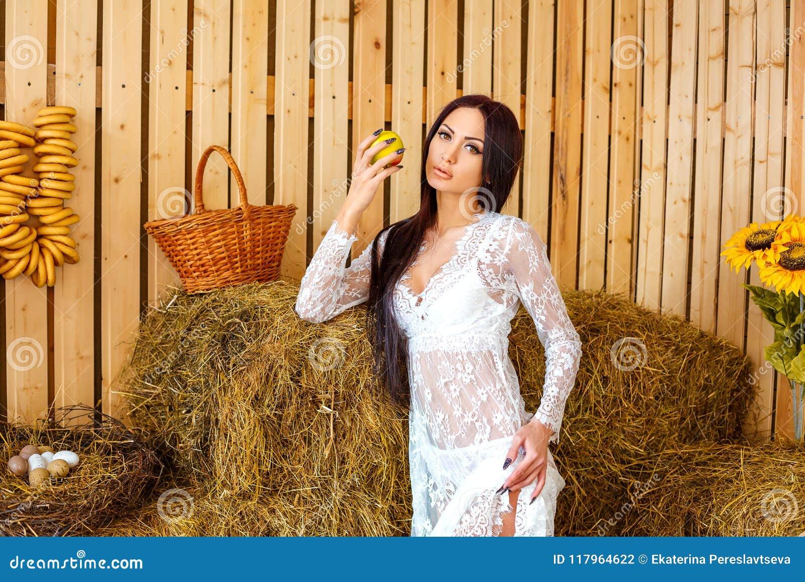 Schöner schlanker Brunette, der im weißen Kleid in der Scheune mit Hayloft, Entspannungskonzept steht