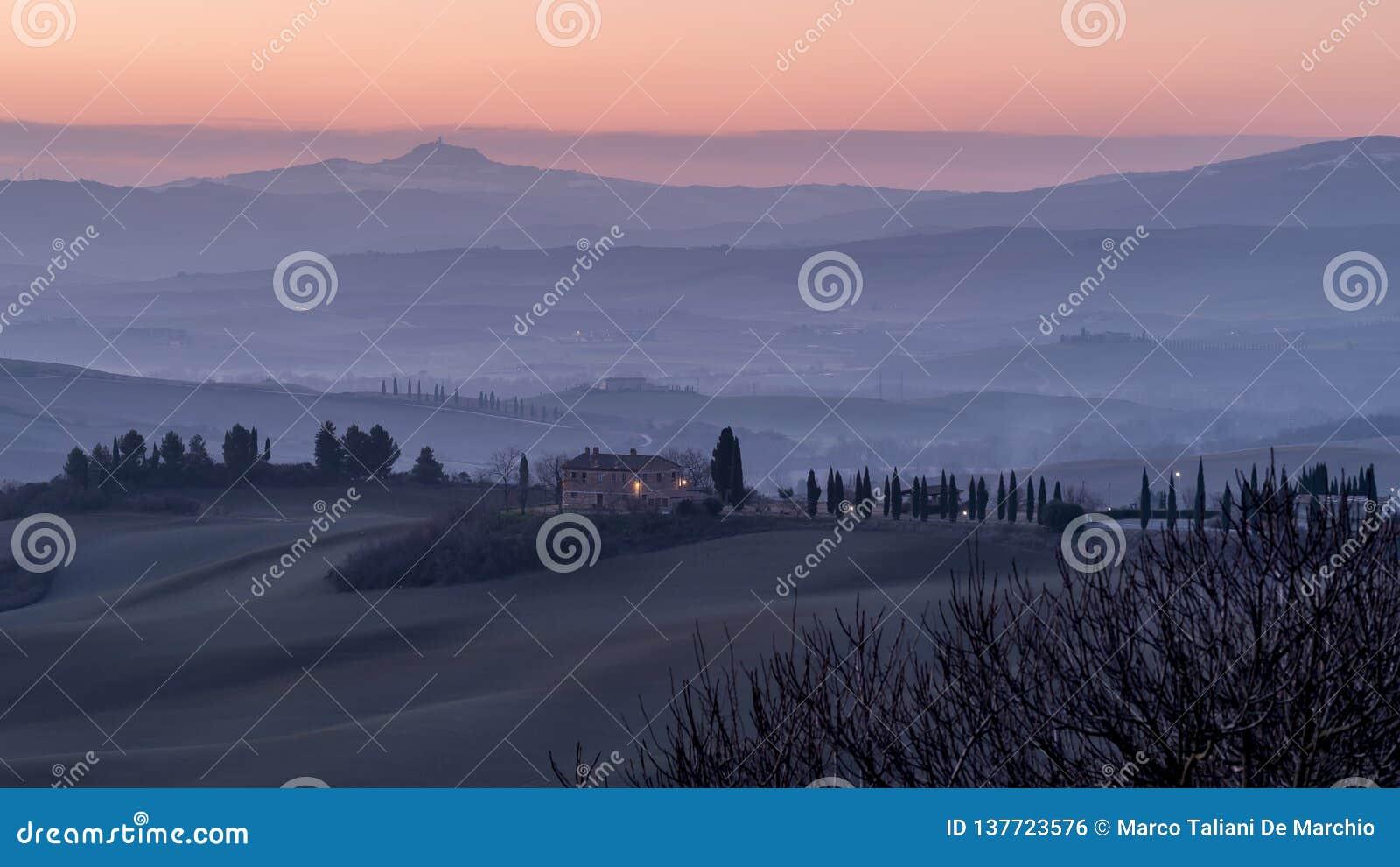 Schöner Sonnenaufgang auf den toskanischen Hügeln zwischen San Quirico d 'Orcia und Rocca di Radicofani, Siena, Italien