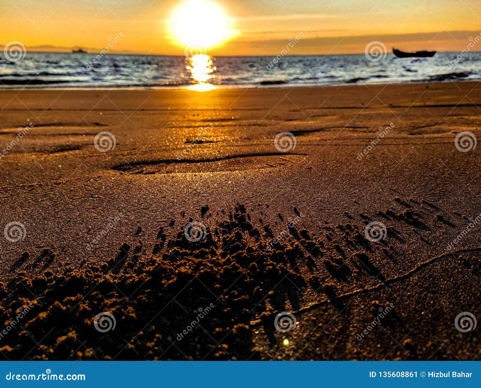 Schöner Sonnenaufgang auf einem Pebble Beach mit Sand und Schritten