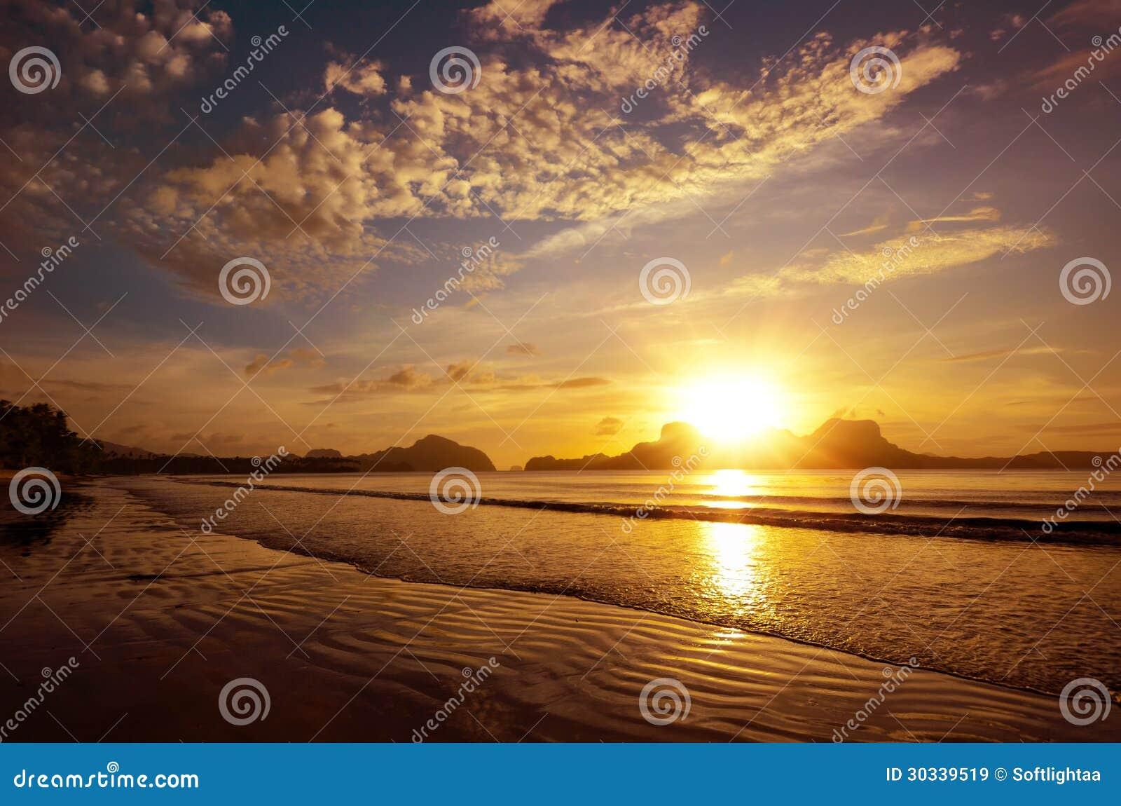 Schöner Sonnenuntergang auf dem Strand unter den Inseln mit der Einstellung