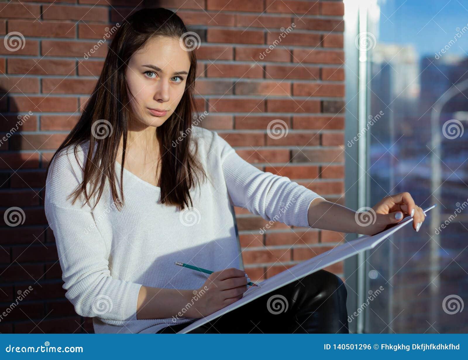 Schöner Student schreibt mit farbigen Bleistiften