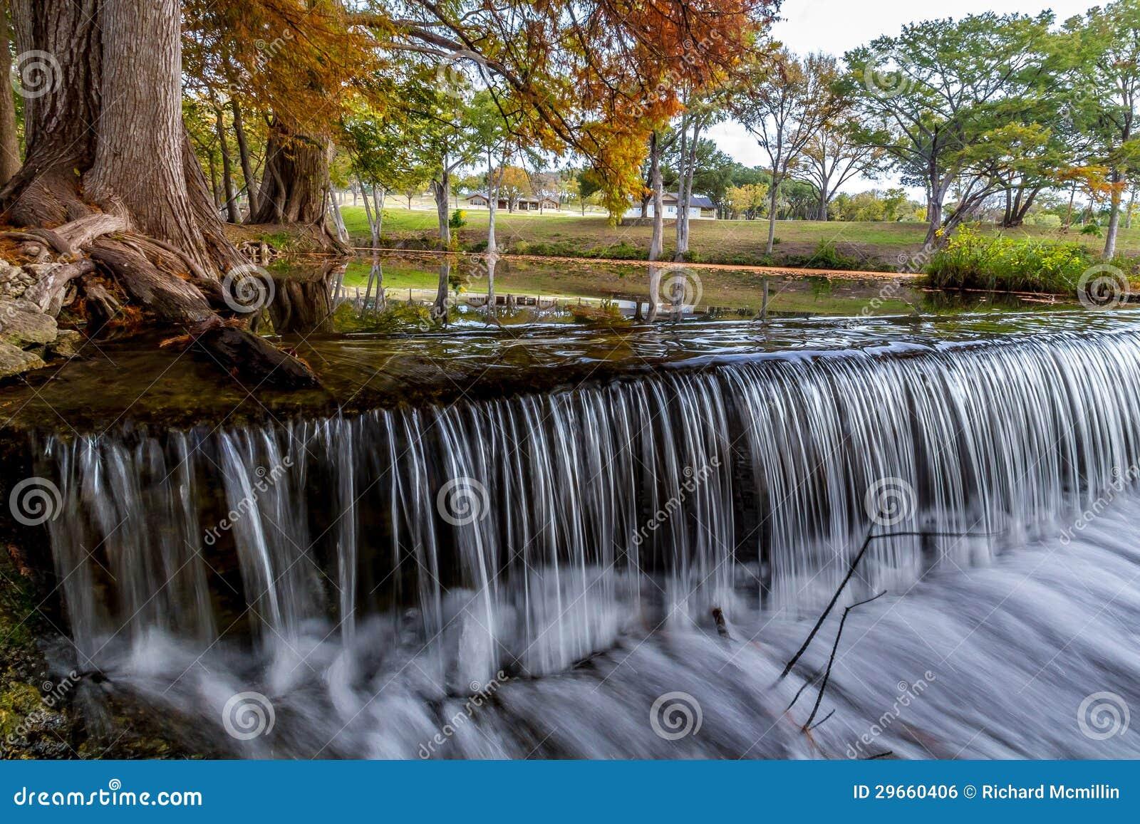 Schöner träumerischer flüssiger Vorhang-Wasserfall nahe Zypern-Bäumen im Texas-Hügel-Land.