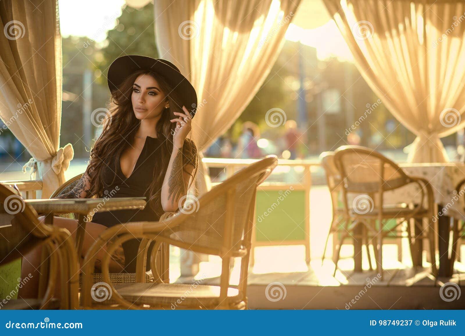 Schöner Zauber tätowierte Brunette in der kleinen Schwarze und in modischem Fedorahut, die im netten Freilichtsommerrestaurant si