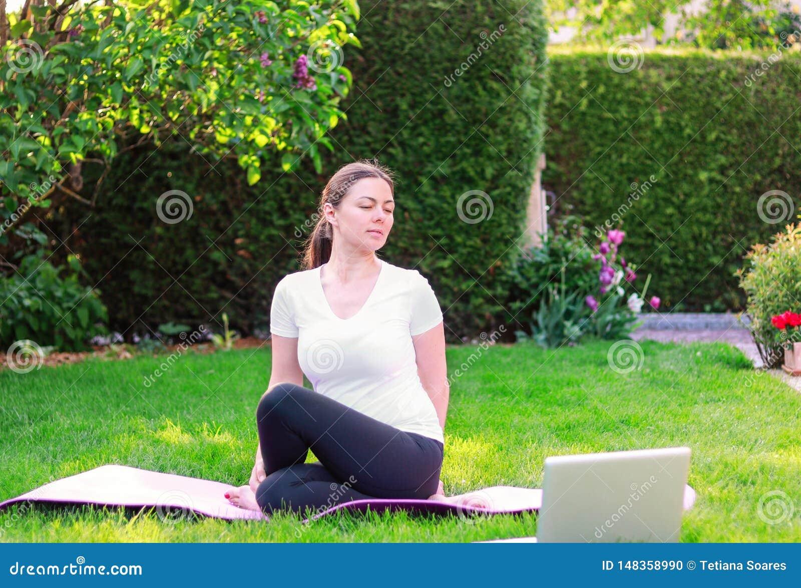 Schönes übendes Yoga der jungen Frau im Garten, der draußen Führer des Online-Tutorials oder Trainer auf Laptop folgt