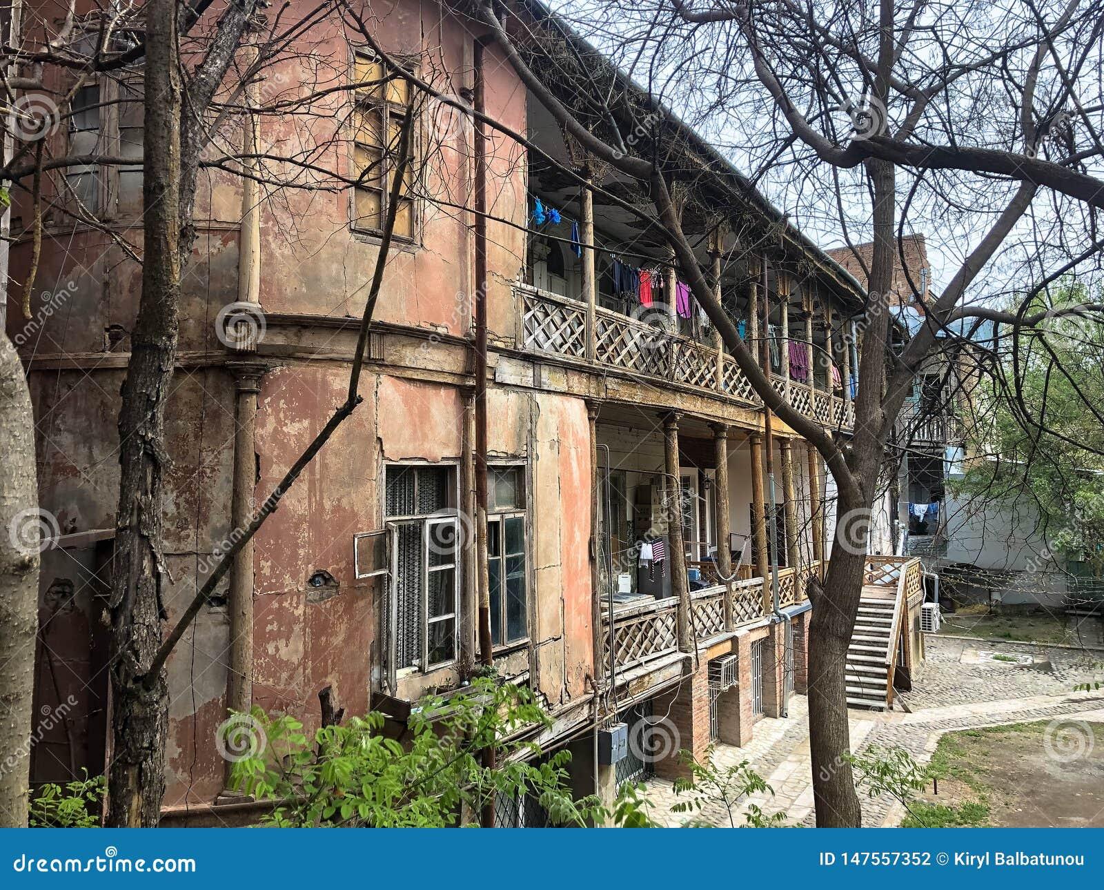 Schönes altes braunes verfallenes dreistöckiges Haus mit Fenstern und Balkonen, Elendsviertelterrassen im alten Stadtgebiet von T