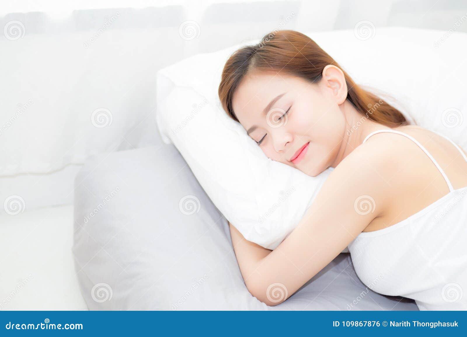 Schönes asiatisches Schlafenlügen der jungen Frau im Bett mit Kopf auf dem Kissen bequem und glücklich