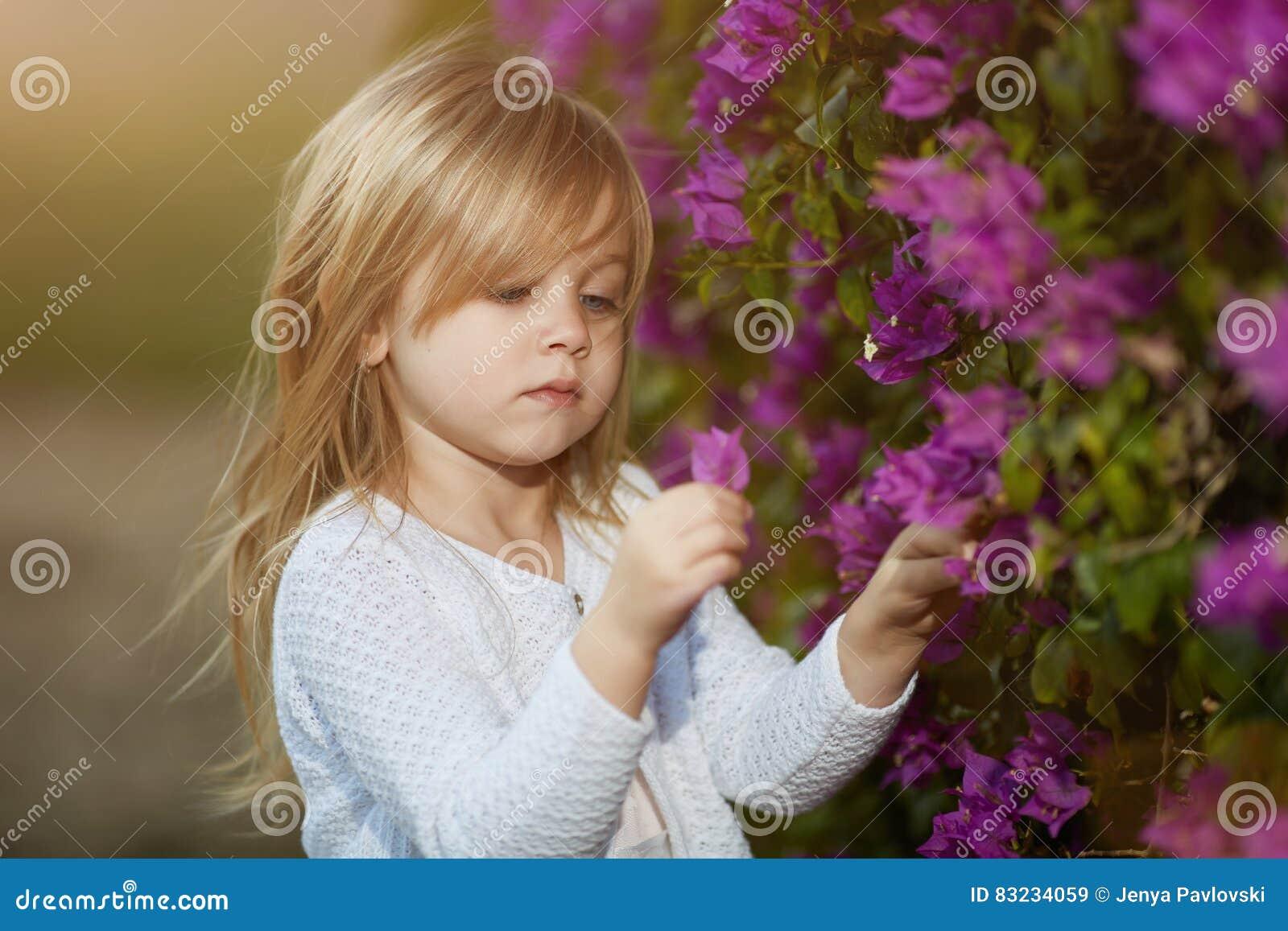 Schönes blondes kleines Mädchen mit riechender Blume des langen Haares