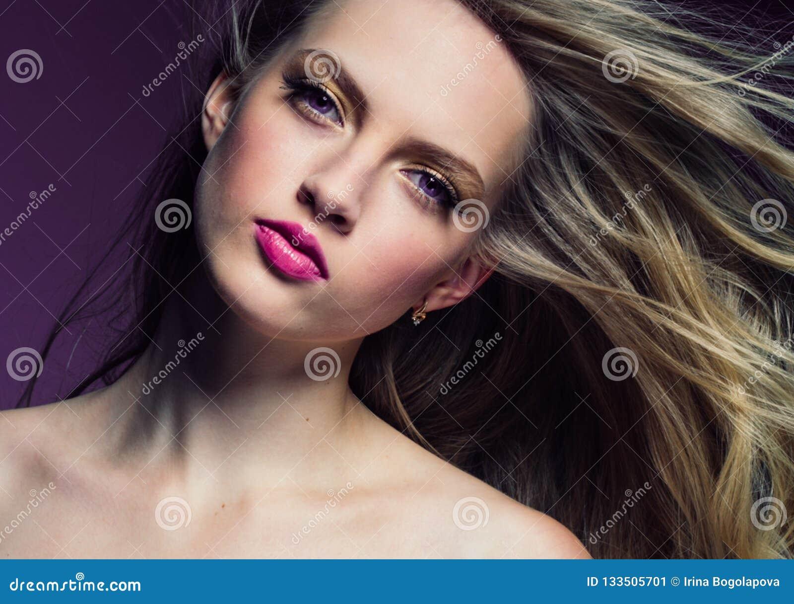 Schönes blondes Mädchen mit dem langen gelockten Haar über purpurrotem backgroun