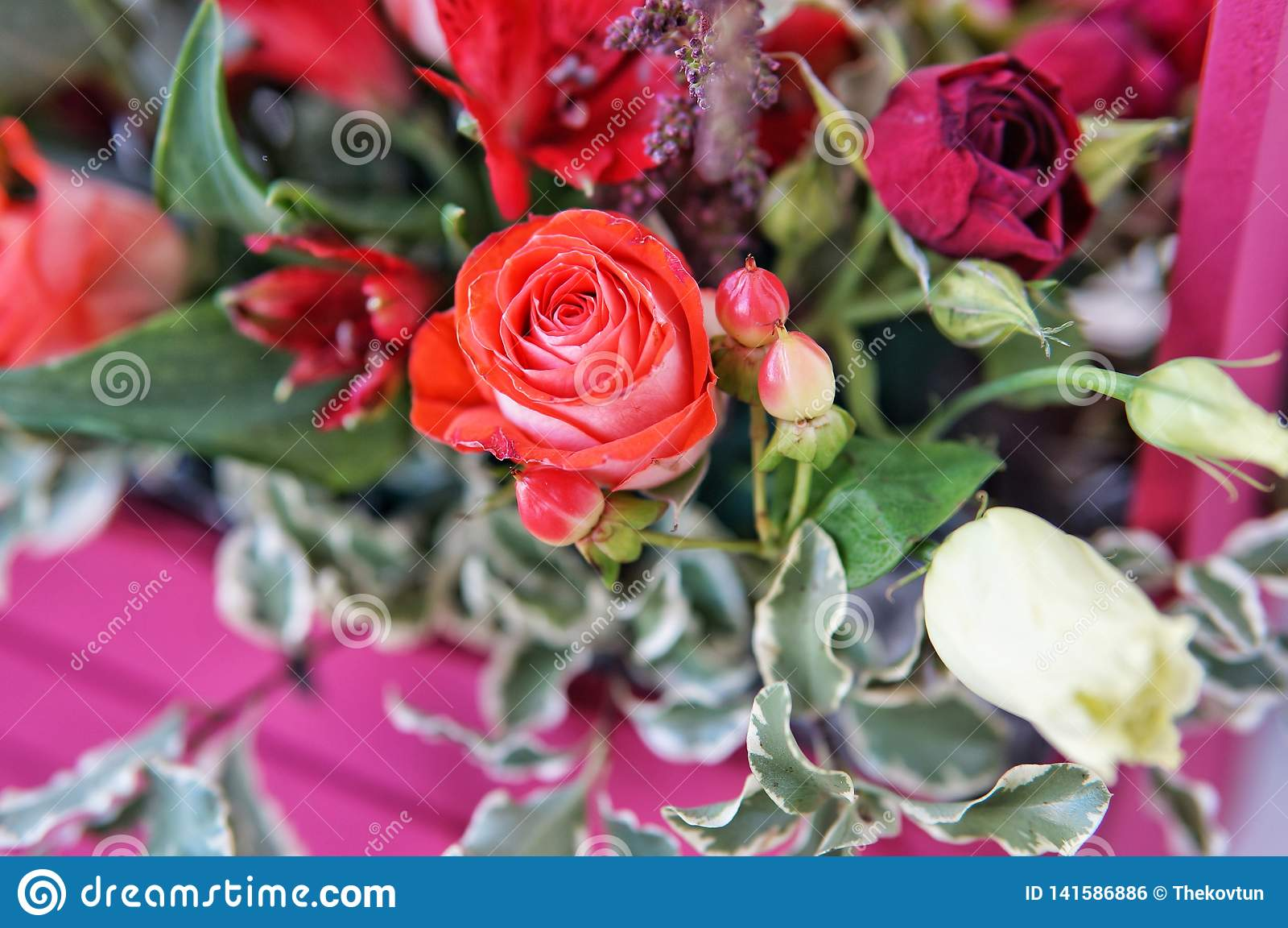 Schönes Blumengesteck von Roten, Rosa- und Burgunder-Blumen in einer rosa Holzkiste