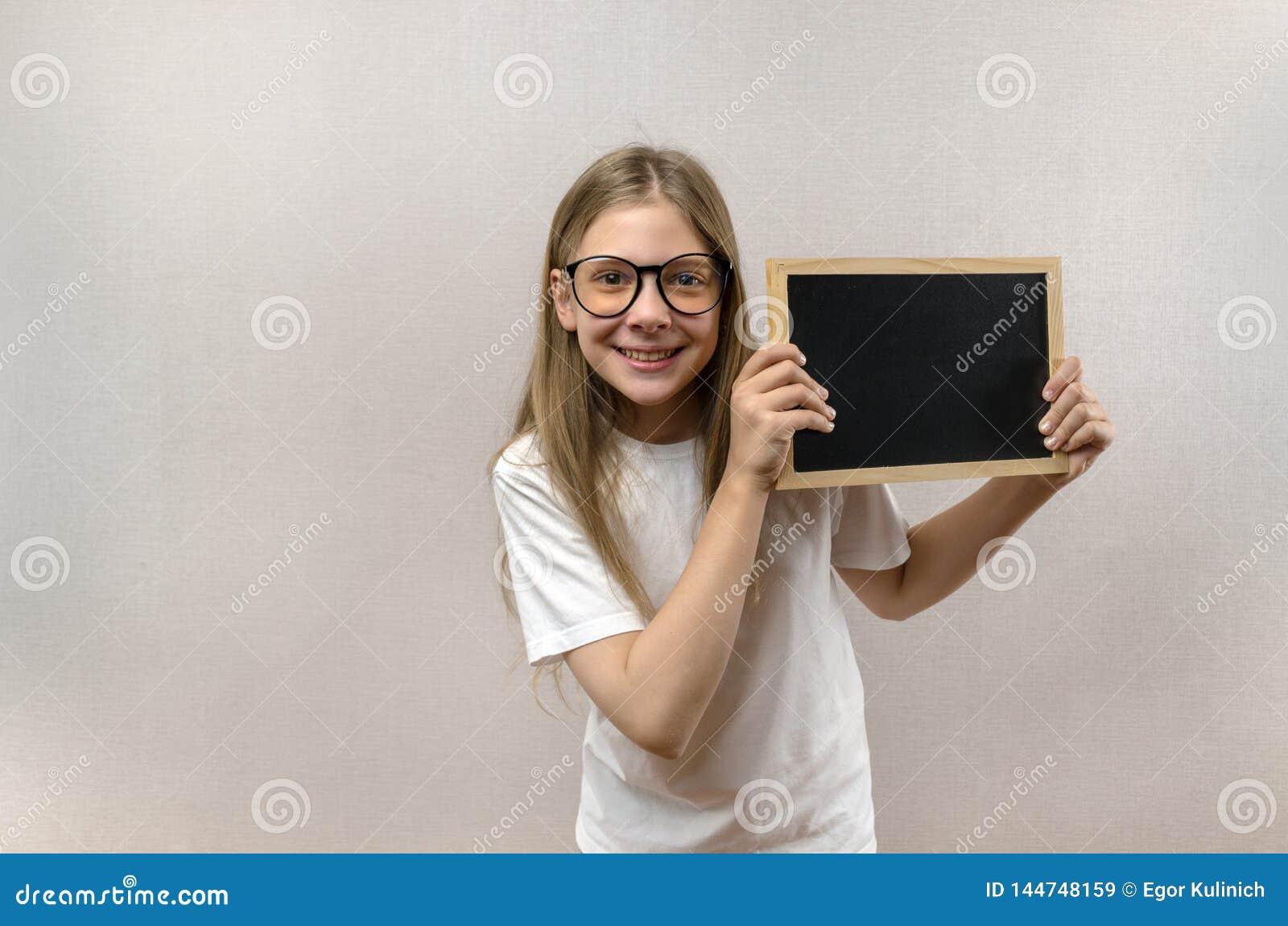 Sch?nes boshaftes M?dchen mit den Gl?sern, die herein ein Zeichen ihre H?nde halten Kopie-Raum