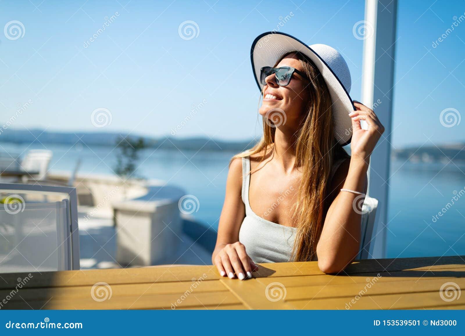 Schönes brunette tragendes Kleid der jungen Frau und Hut, Lächeln im Freien