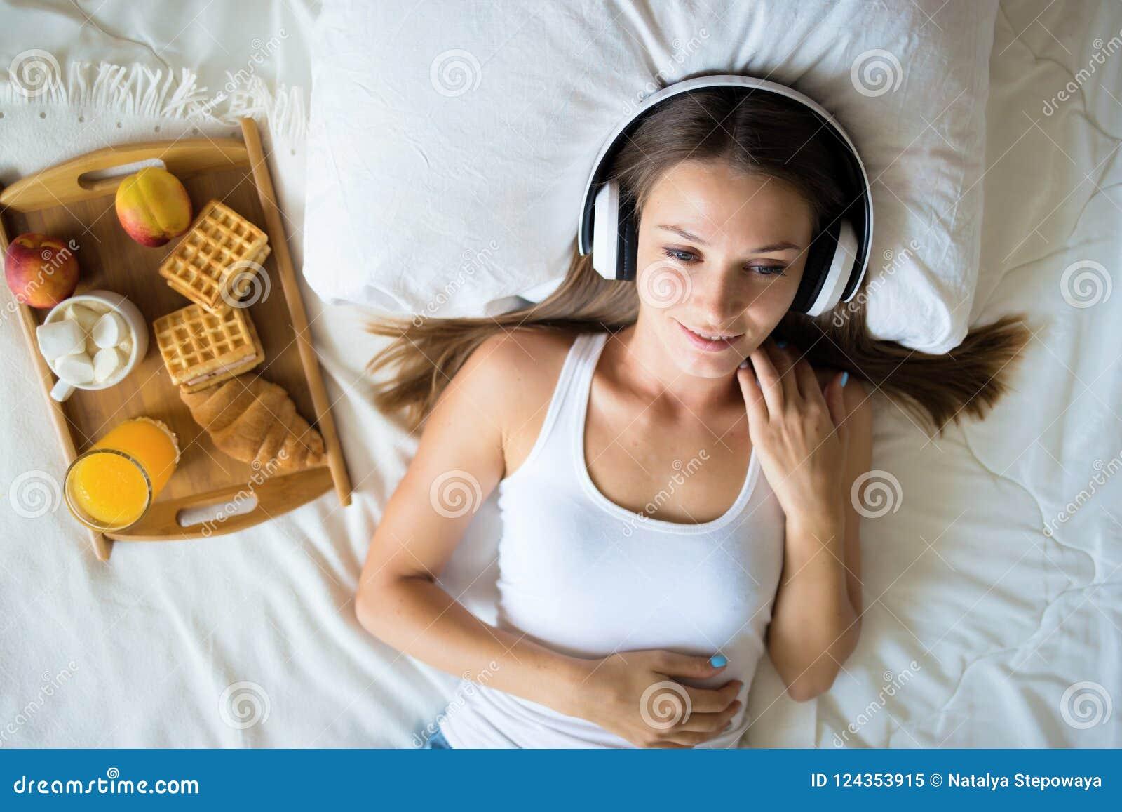 Schönes Brunettemädchen, das Musik auf Kopfhörern im Bett hört Frühstücks-Frau morgens