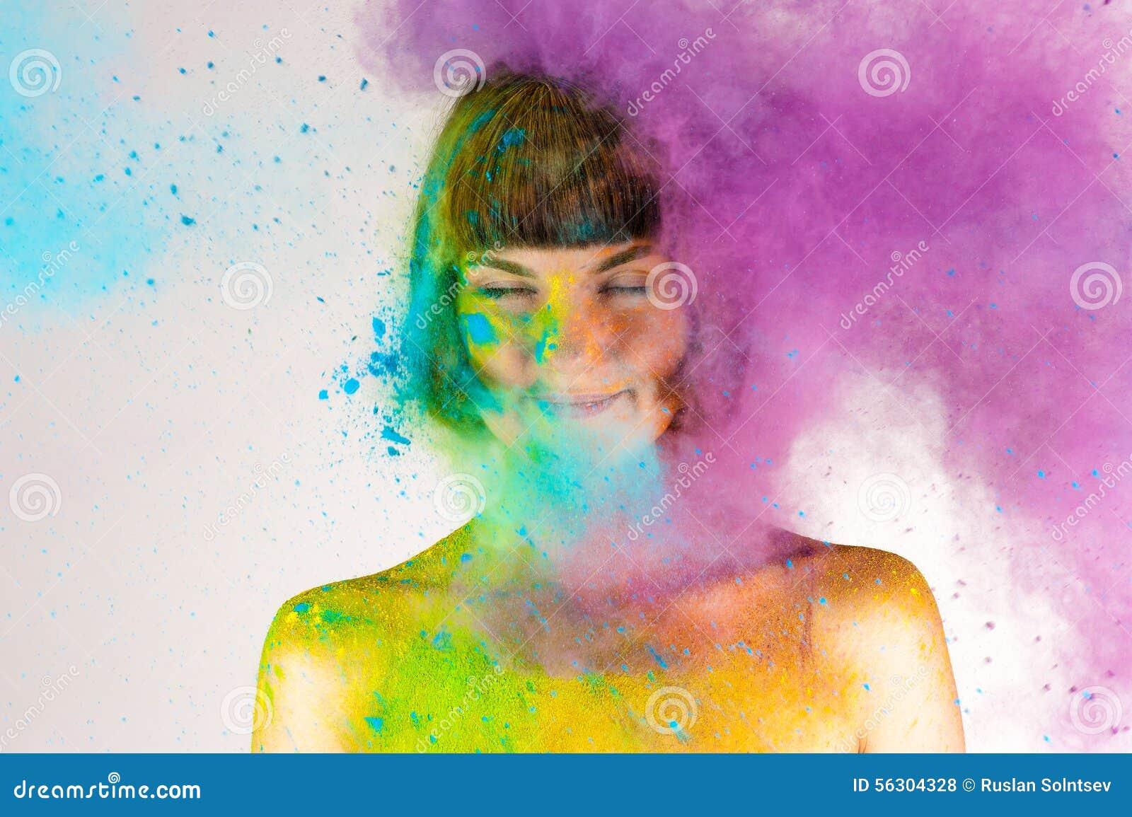 Schönes Brunettemädchen in den Farben Holi auf einem Weiß