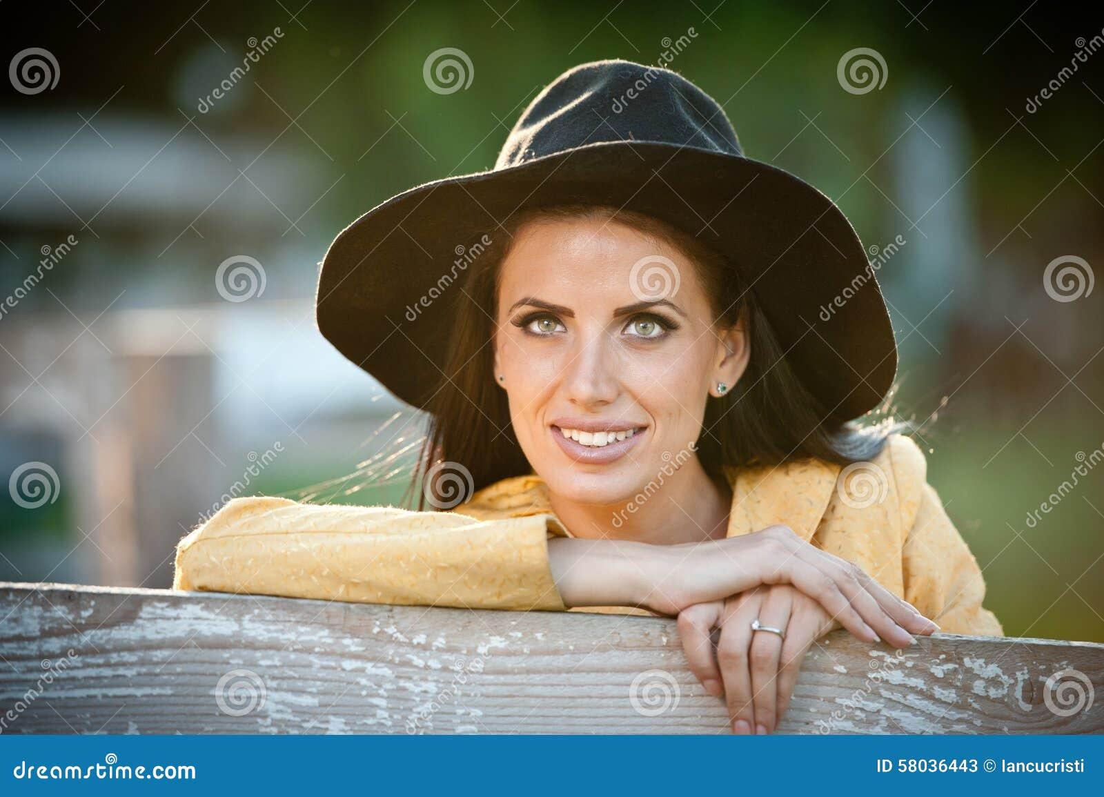Schönes Brunettemädchen mit Landblick nahe einem alten Bretterzaun Attraktive Frau mit schwarzem Hut und gelbem Mantel