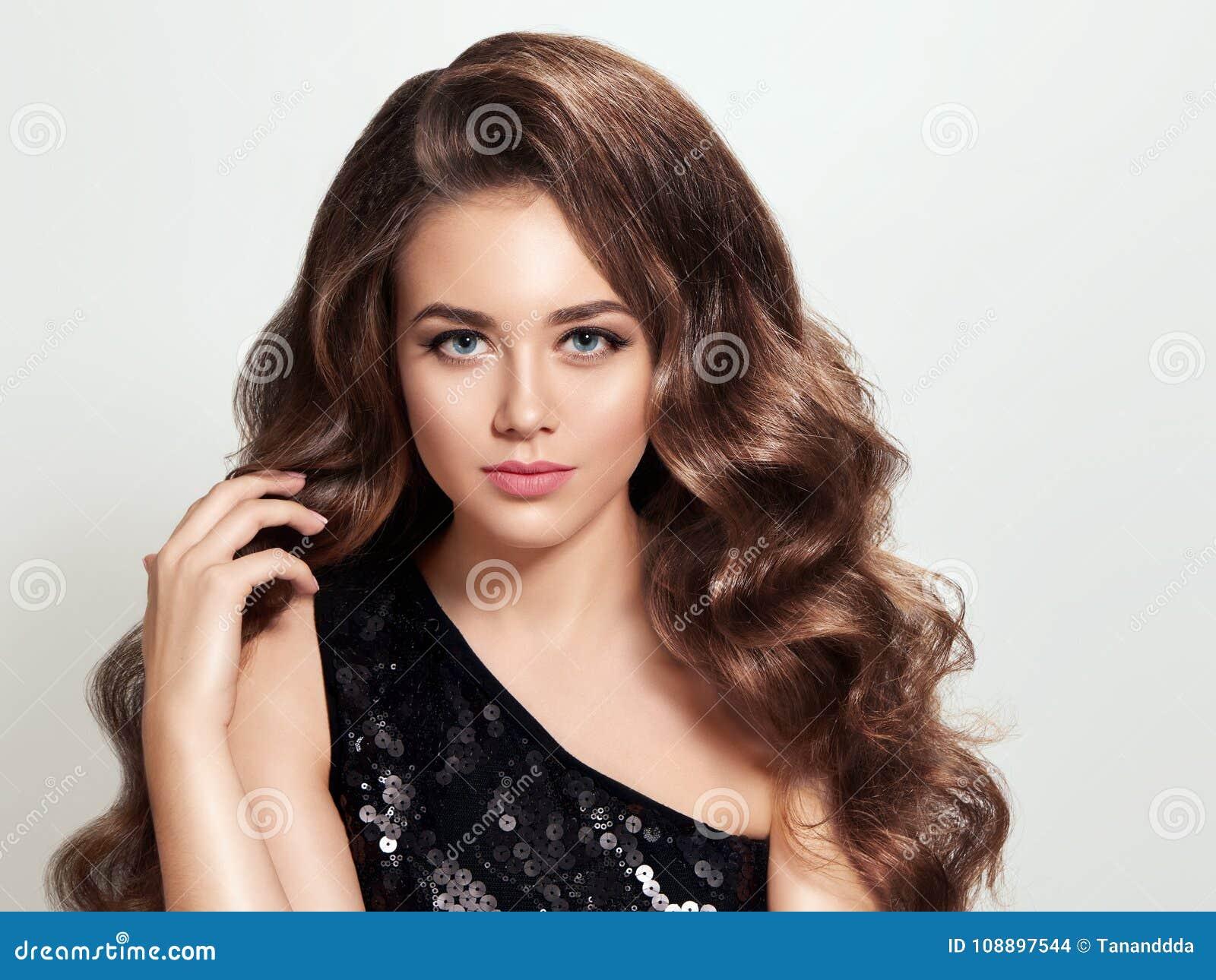 Schönes Brunettemädchen mit lang und glänzendes gelocktes Haar des Volumens
