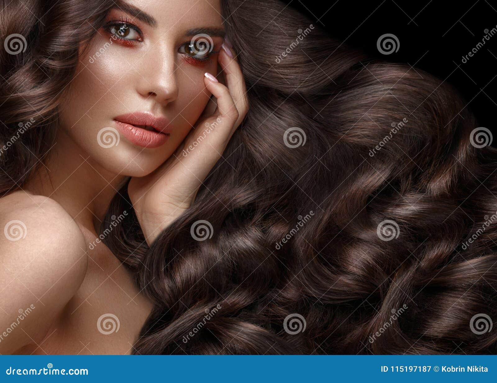 Schönes Brunettemodell: Locken, klassisches Make-up und volle Lippen Das Schönheitsgesicht