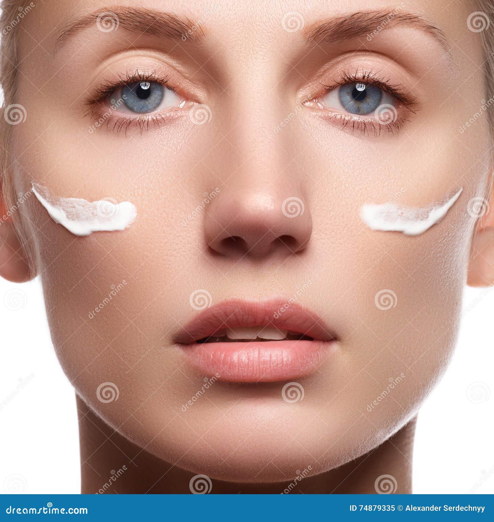 Schönes Gesicht der jungen Frau mit kosmetischer Sahne auf einer Backe