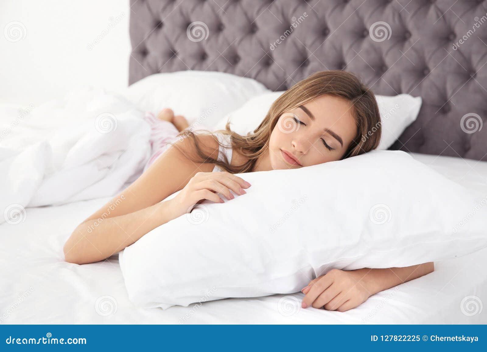 Schönes jugendlich Mädchen, das mit bequemem Kissen im Bett schläft