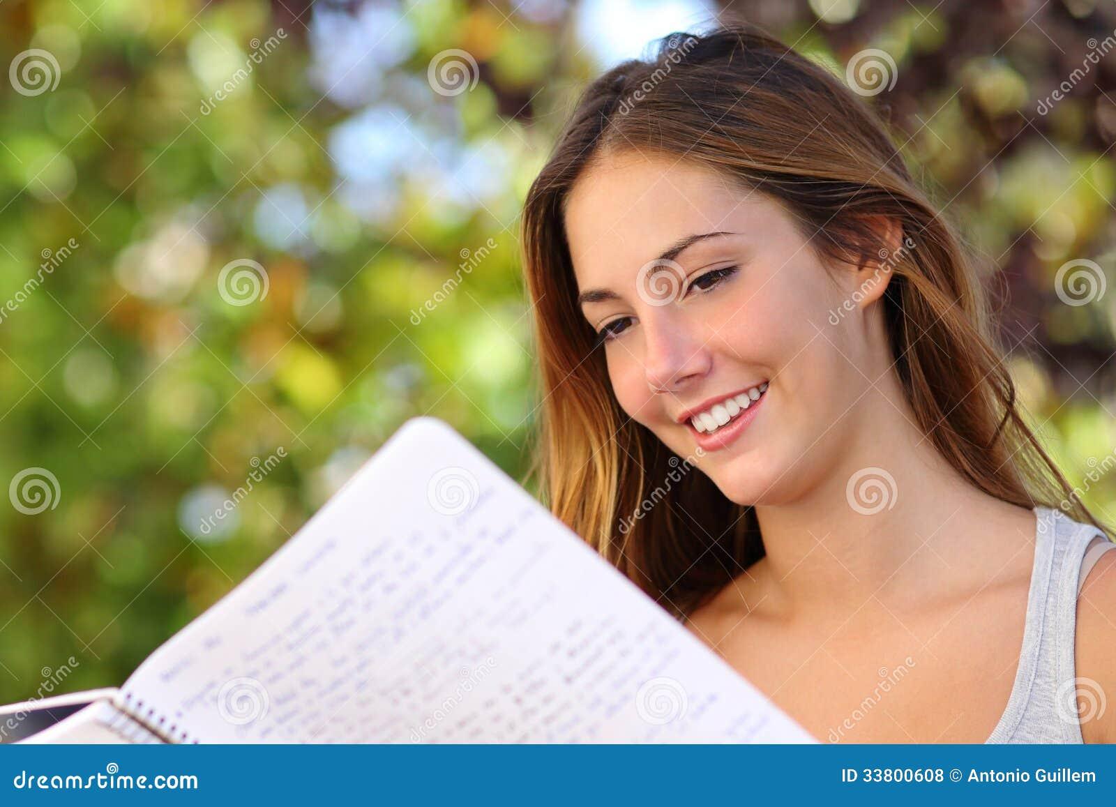 Schönes Jugendlichmädchen, das ein Notizbuch lesend im Freien studiert