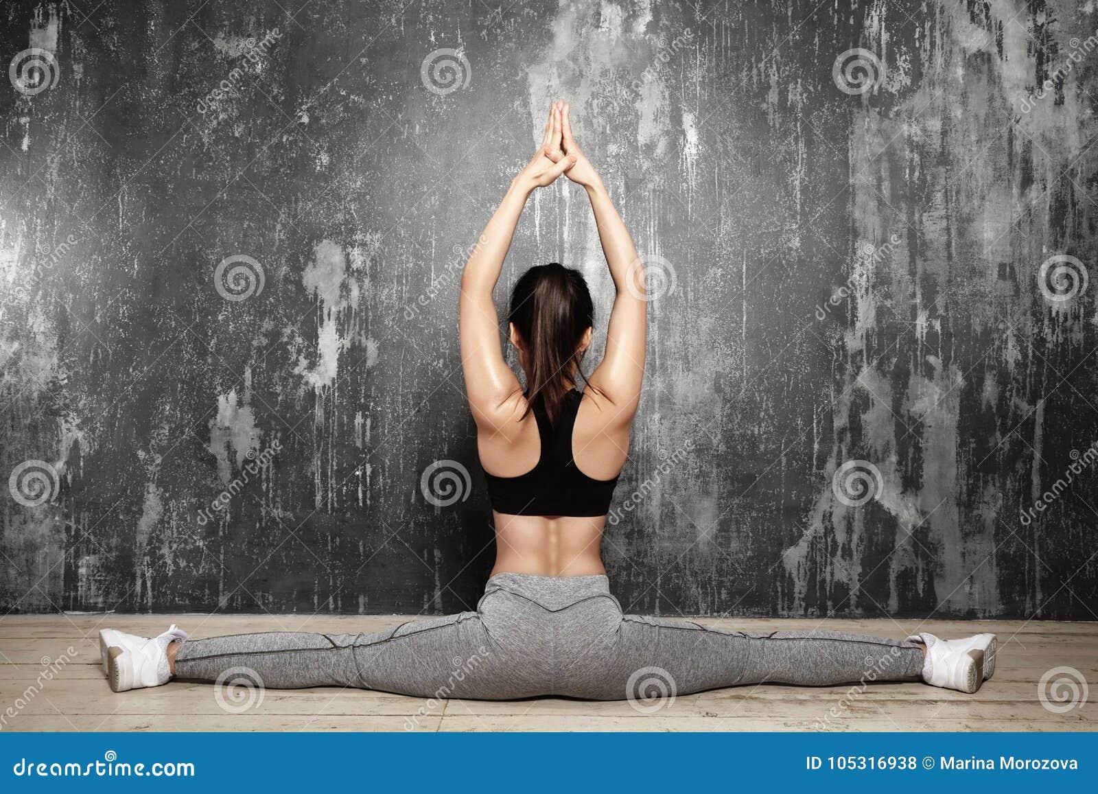 Schönes junges asiatisches Frauen-Ausarbeiten, Pilates-Übung in der Sportkleidung tuend Spalten mit Yoga Asana, dehnend aus