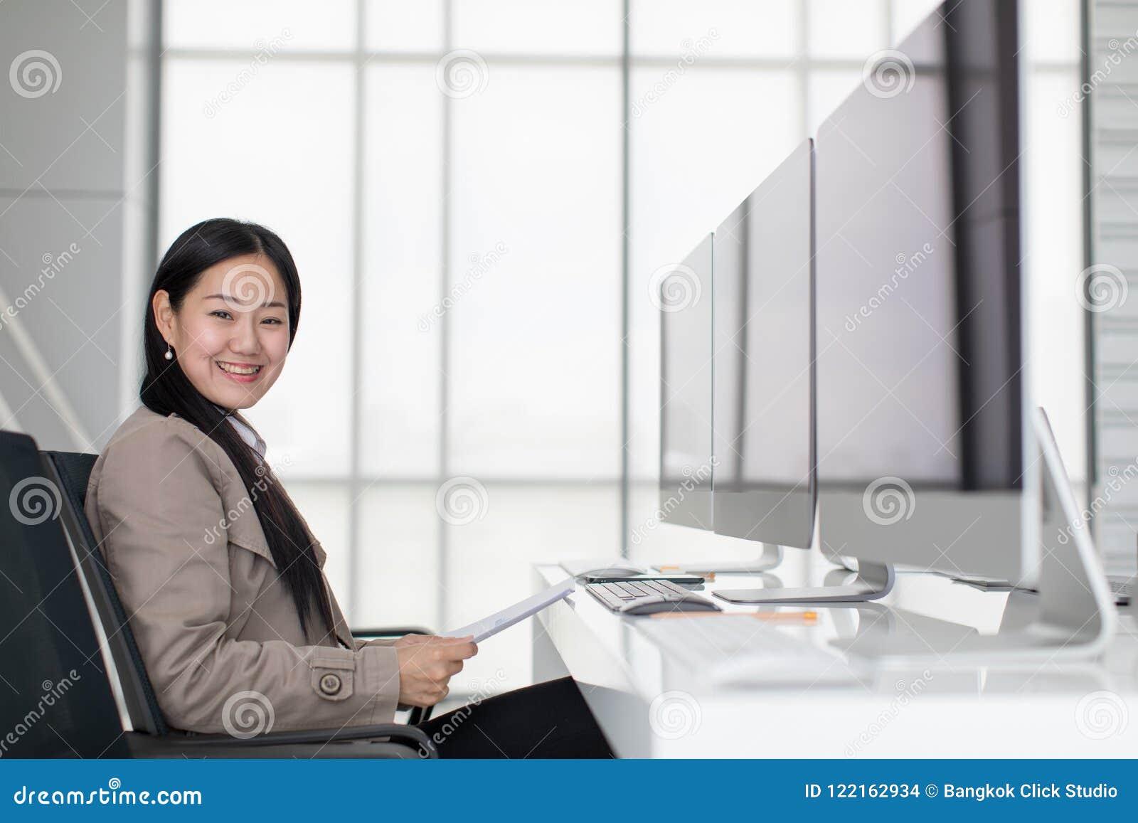 Schönes junges asiatisches Sitzen im modernen Büro glücklich, dort a