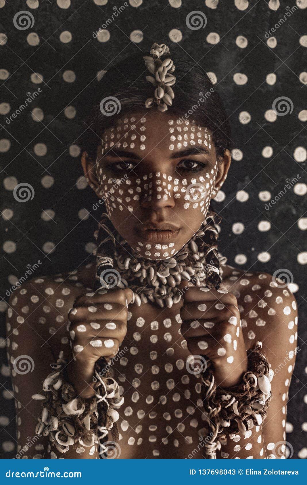 Schönes junges attraktives modernes vorbildliches Porträt mit traditioneller Verzierung auf Haut und Gesicht