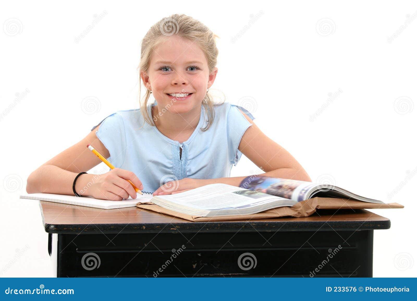 Schönes junges Mädchen, das am Schule-Schreibtisch sitzt