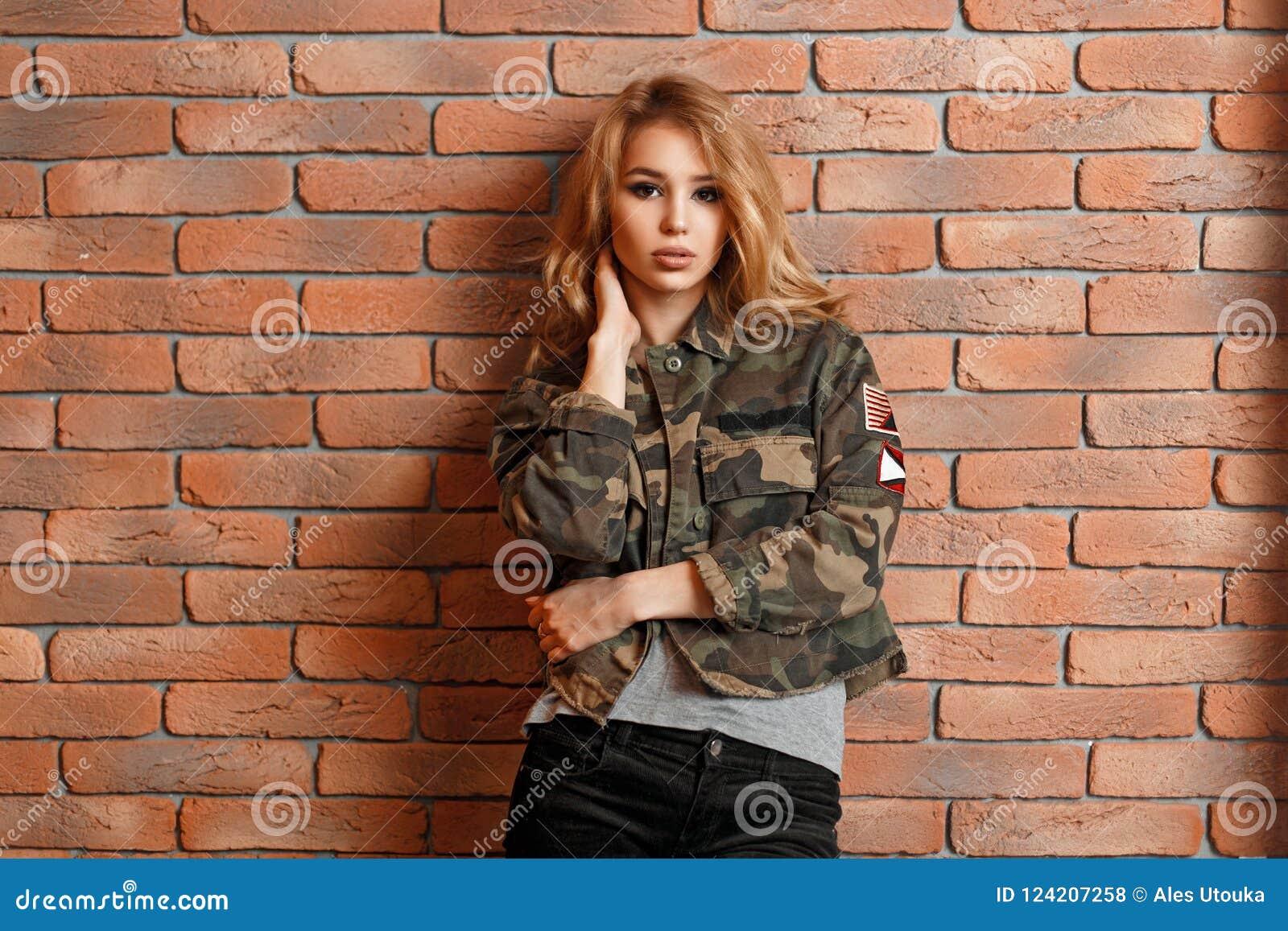 Schönes junges Mädchen in der Militärjacke nahe Wand des roten Backsteins