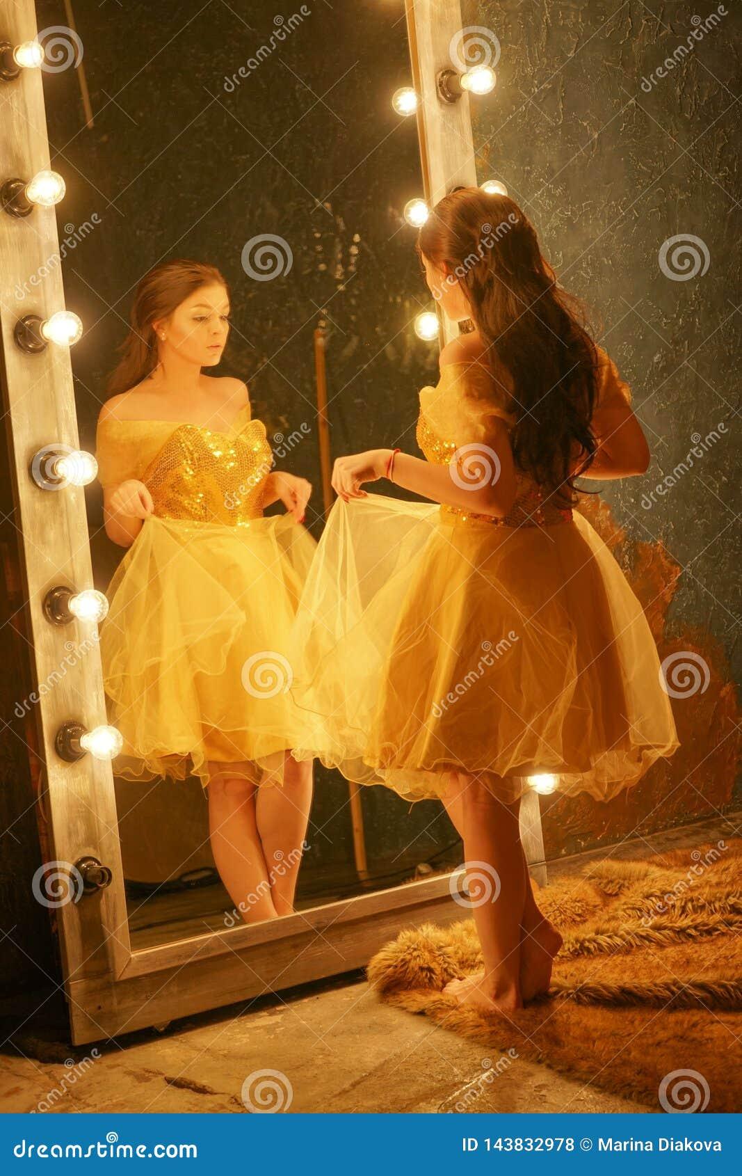 Schönes junges Mädchen in einem Goldabendkleid steht auf einer Pelzwolldecke nahe einem großen Spiegel in einem Rahmen mit Lichte