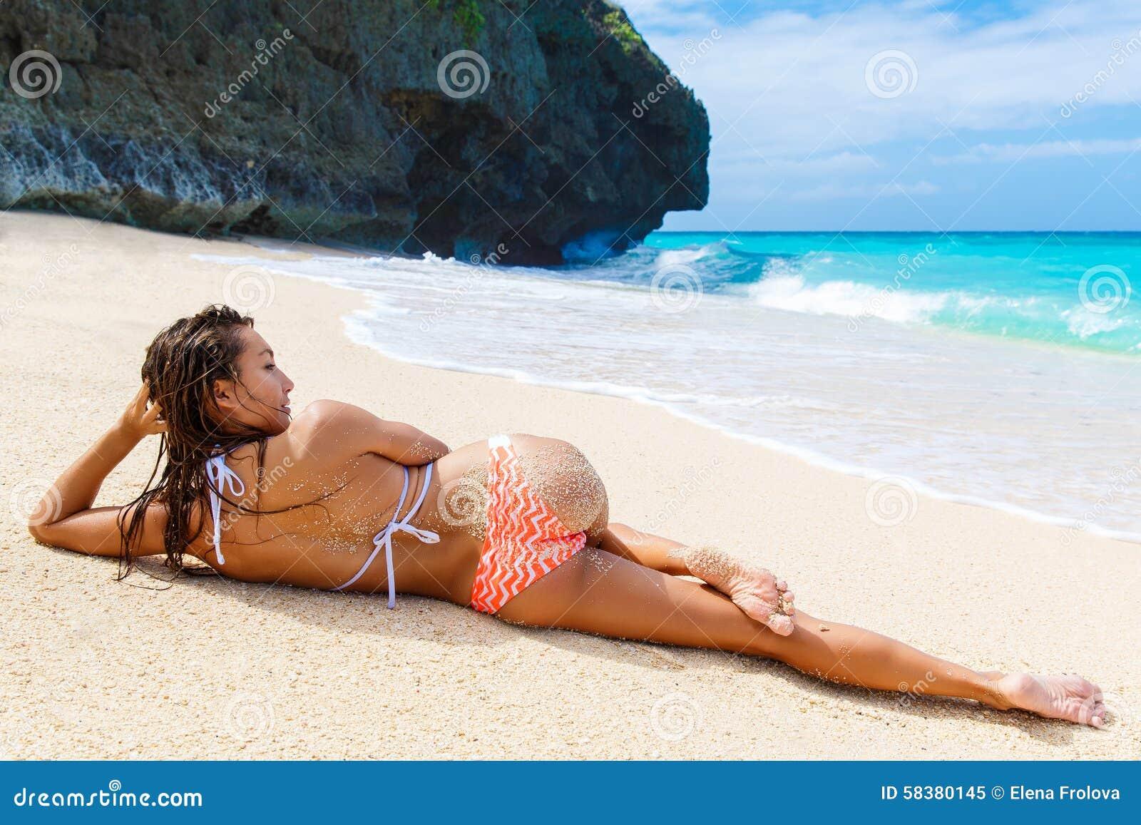 Schönes junges Mädchen im Bikini auf einem tropischen Strand Blaues Meer herein