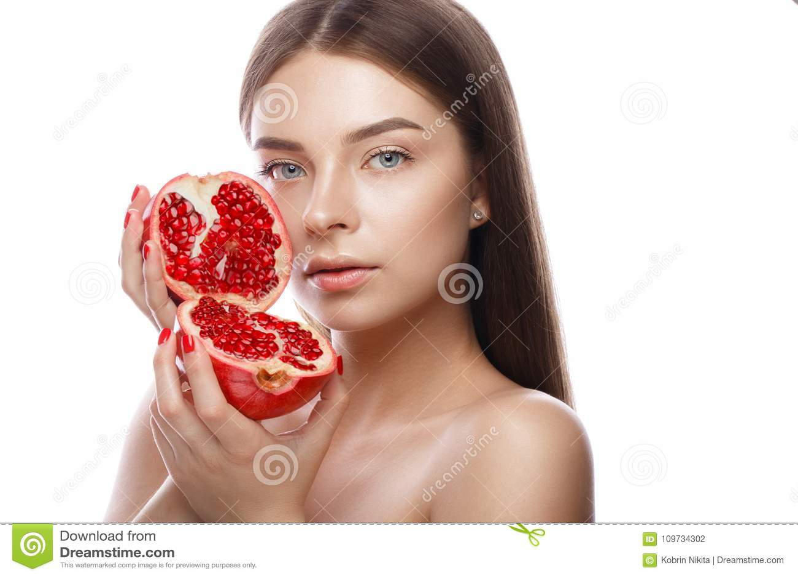 Schönes junges Mädchen mit einem hellen natürlichen Make-up und perfekte Haut mit Granatapfel in ihrer Hand Schönes lächelndes Mä
