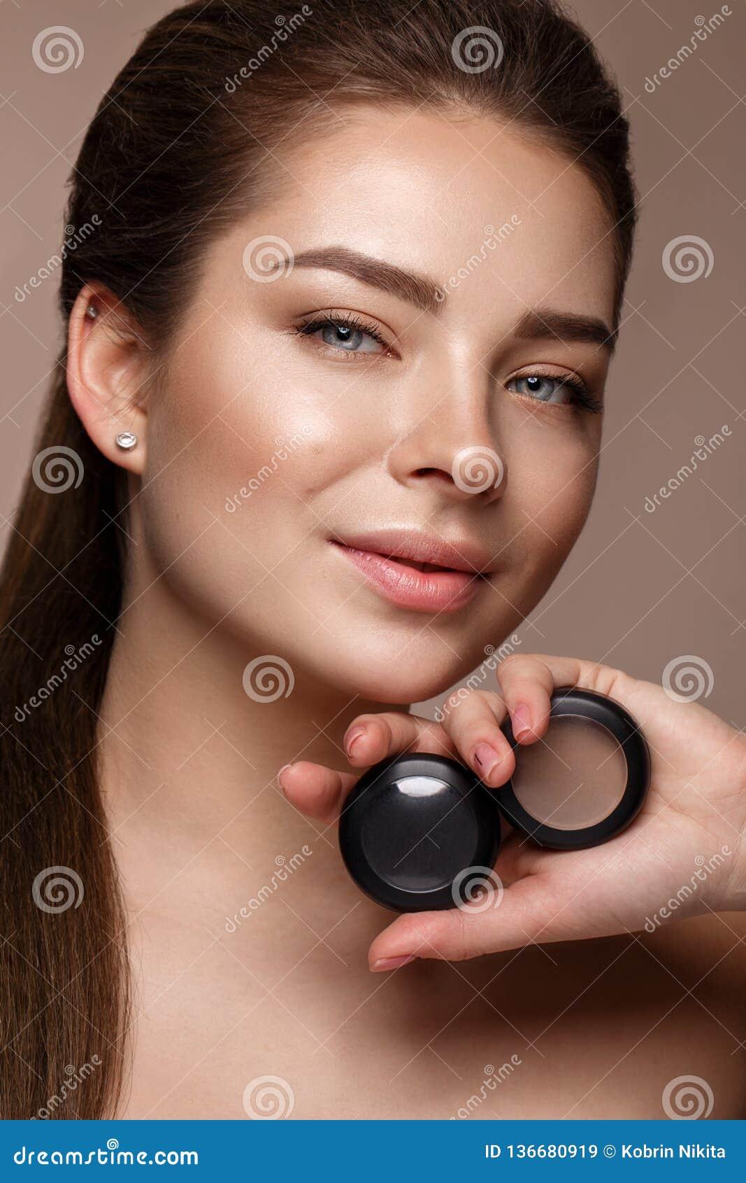 Schönes junges Mädchen mit natürlichem nacktem Make-up mit Kosmetik in den Händen Schönes lächelndes Mädchen