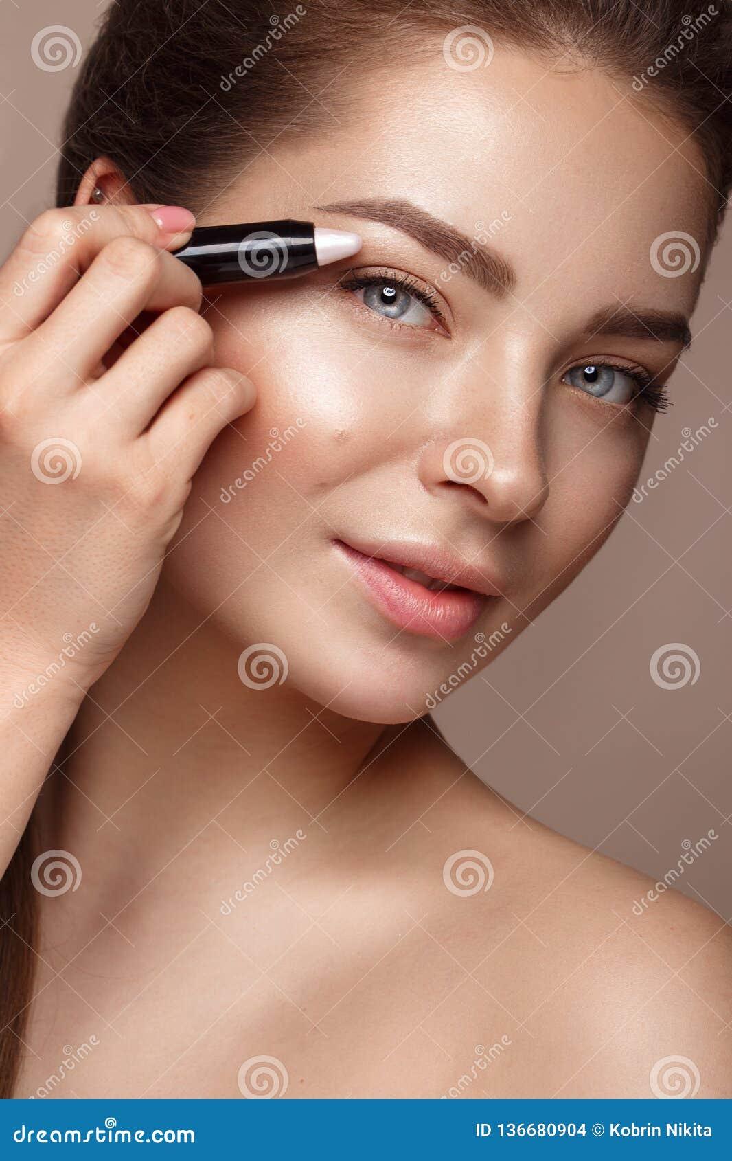 Schönes junges Mädchen mit natürlichem nacktem Make-up und Leuchtmarkerbleistift Schönes lächelndes Mädchen
