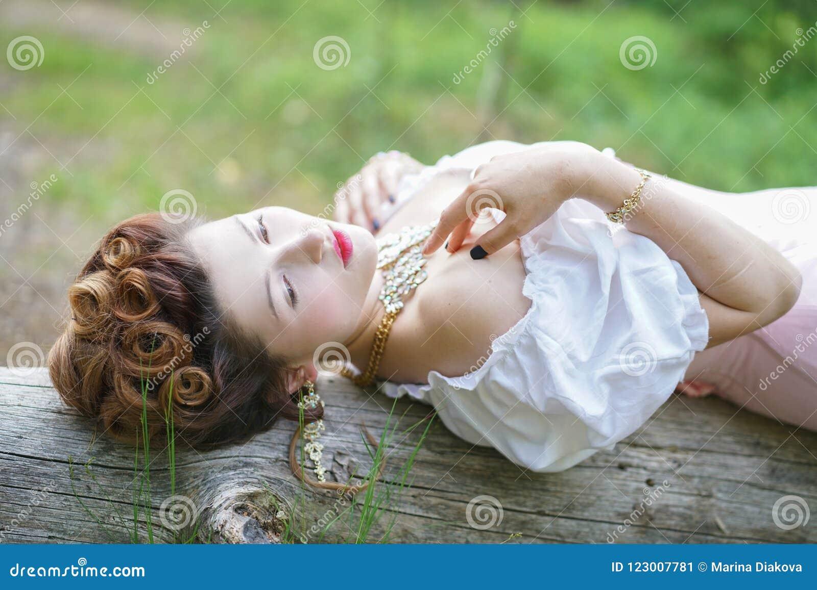 Schönes junges molliges Mädchen, das im mittelalterlichen Retro- Korsett und in der weißen Weinlesewäsche im Wald aufwirft