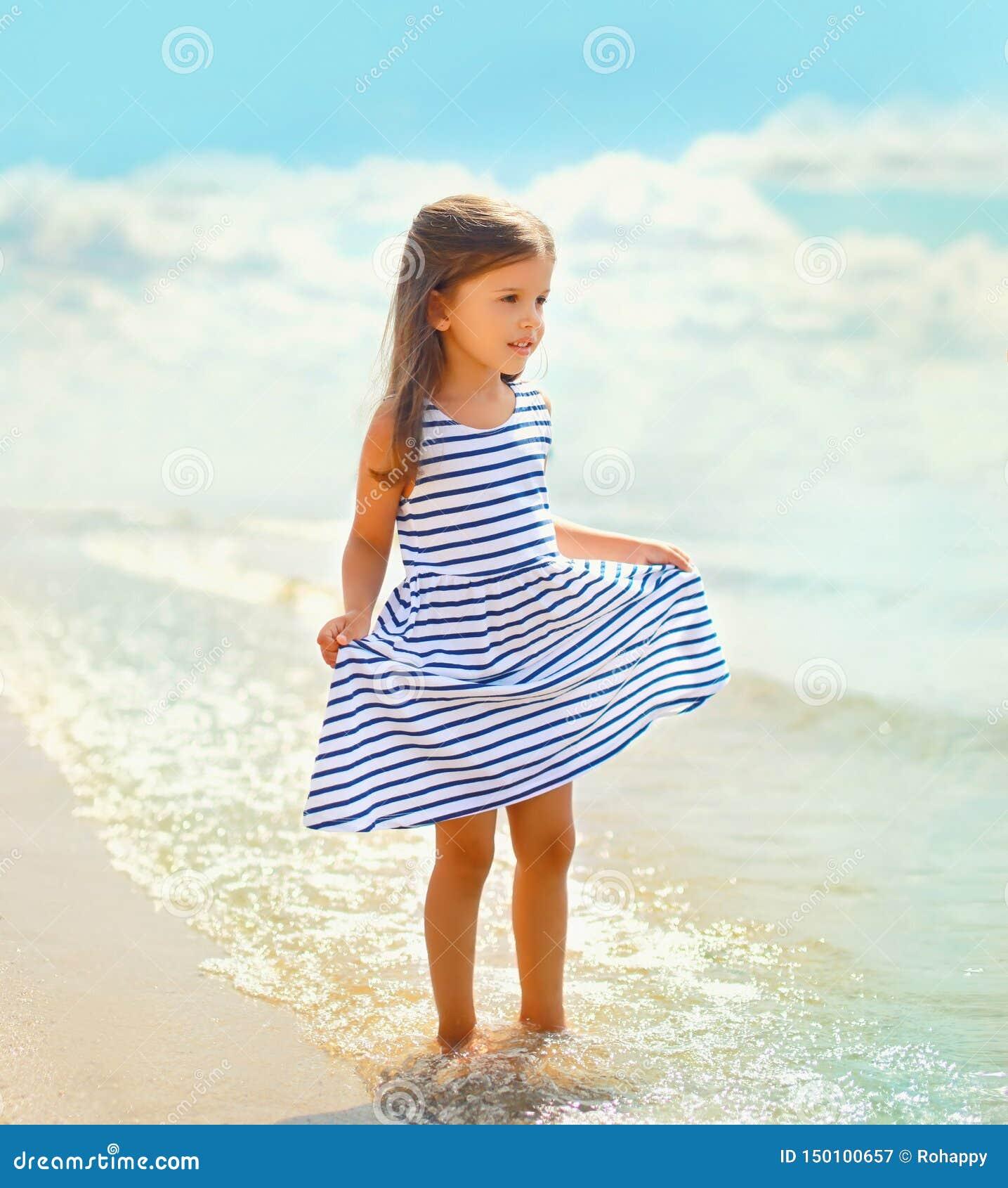 Schönes Kind des kleinen Mädchens des Sommerporträts in gestreiftem Kleid gehend auf Strand nahe Meer