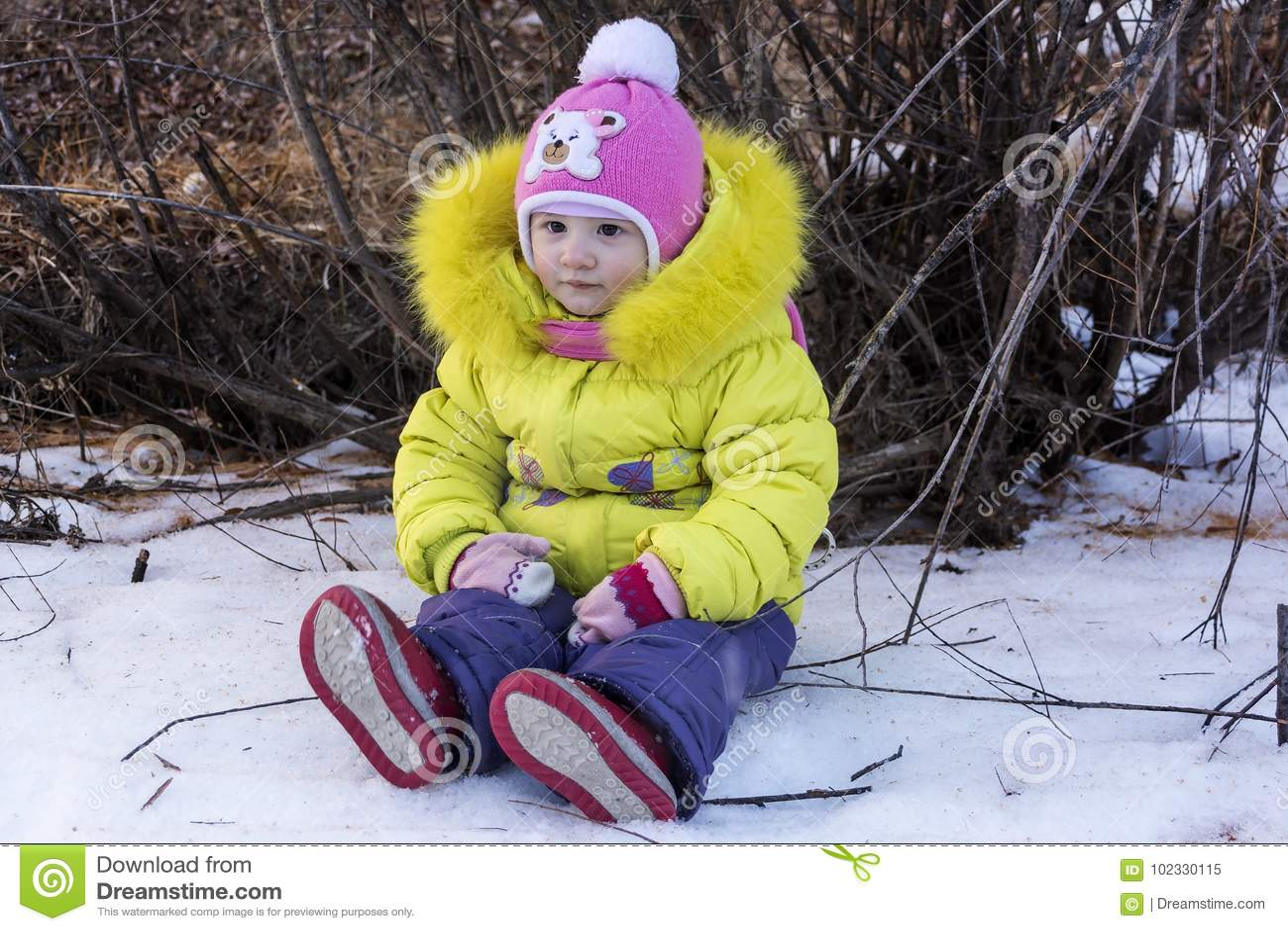 Schönes kleines Baby ein Sitzen auf frischem Schnee an einem sonnigen Wintertag