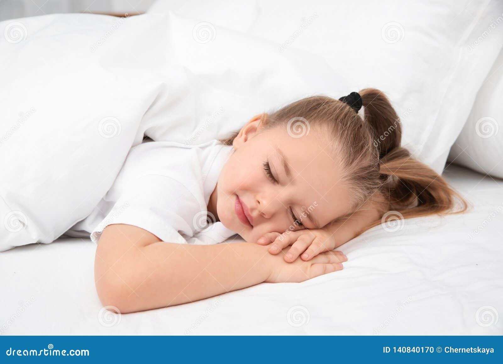 Schönes kleines Mädchen, das im Bett schläft bedtime