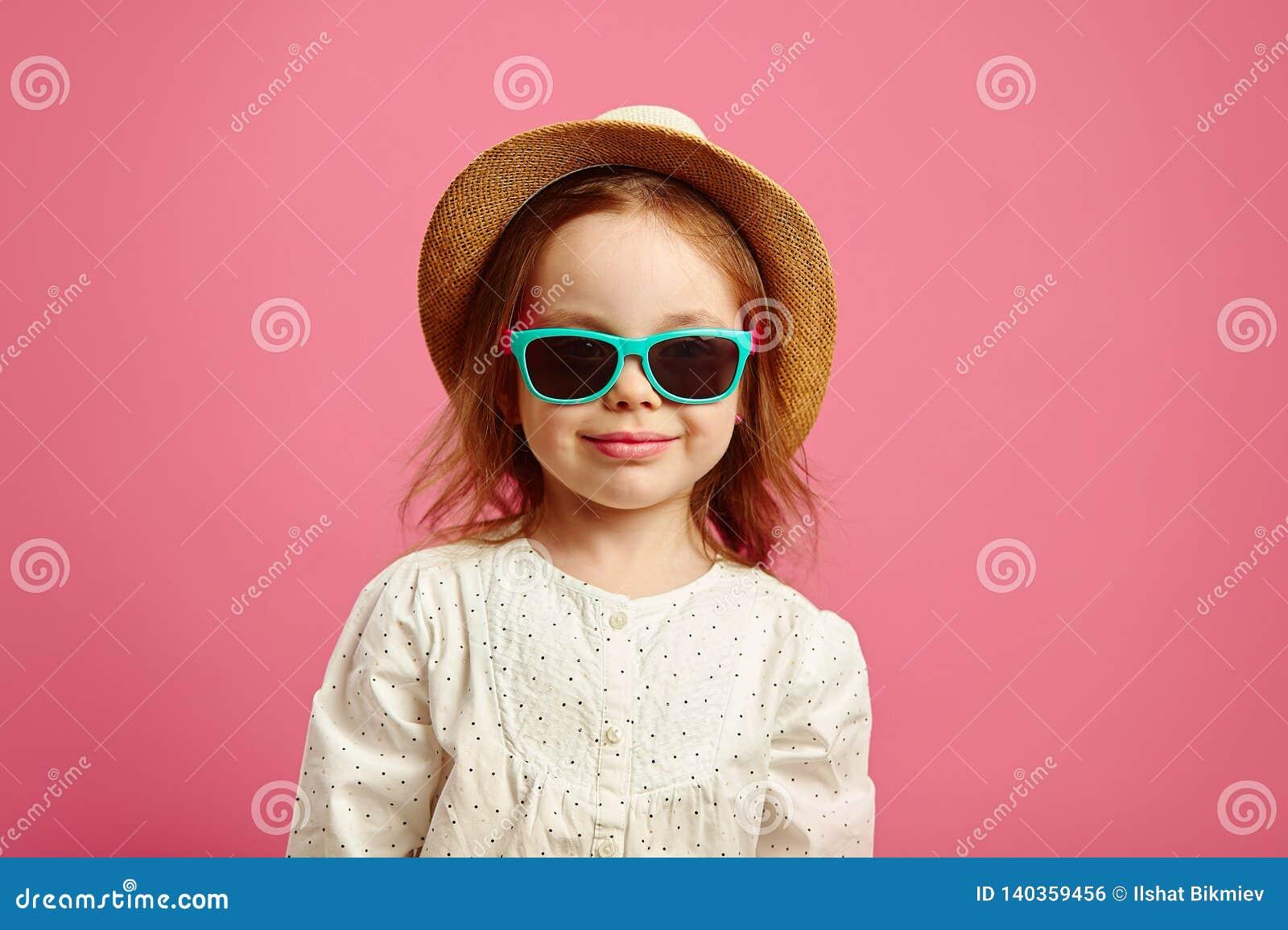 Schönes kleines Mädchen im Strohhut und in der Sonnenbrille, Nahaufnahmeporträt auf rosa lokalisiert