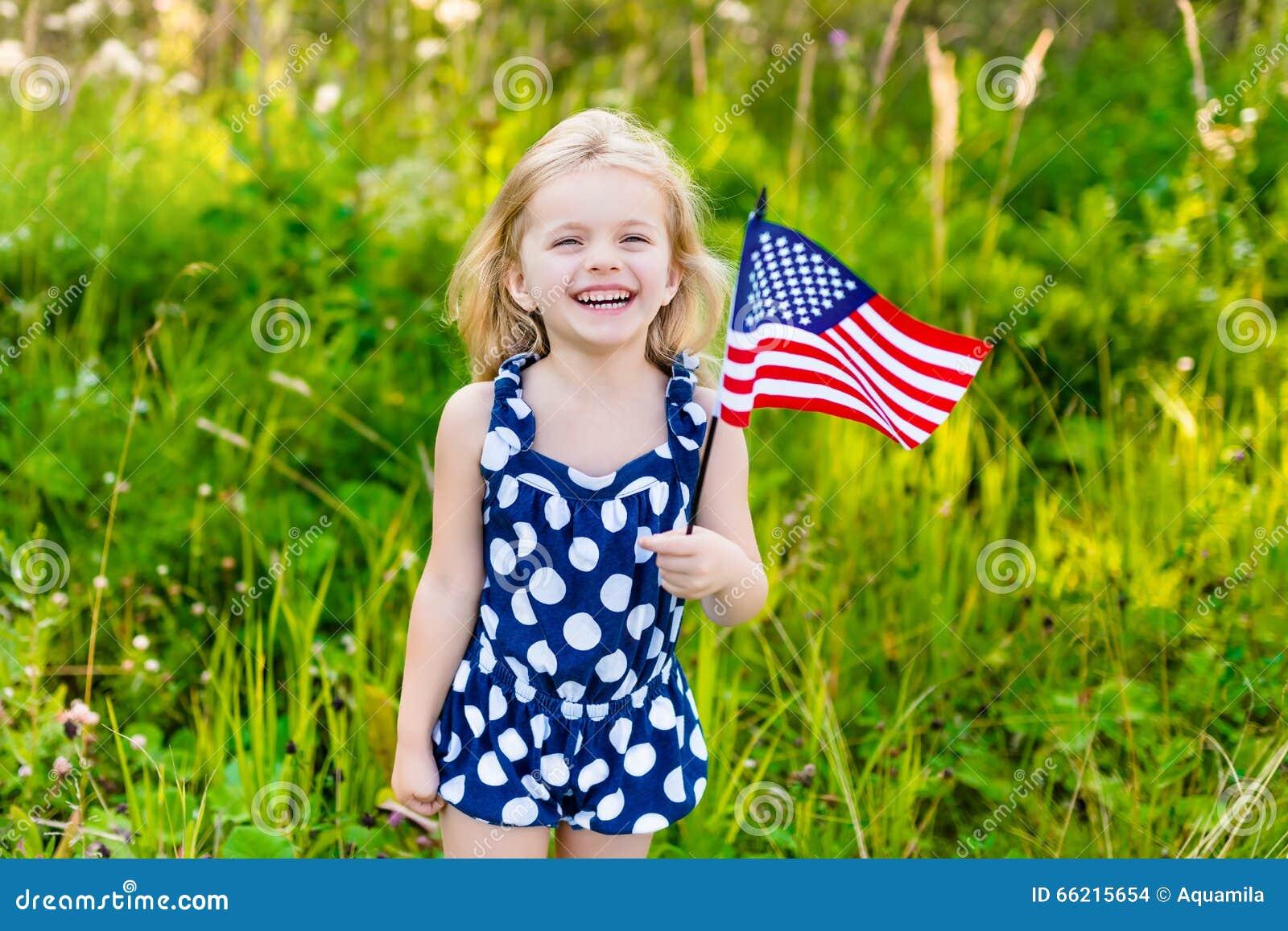 Schönes kleines Mädchen mit dem langen gelockten blonden Haar mit amerikanischer Flagge