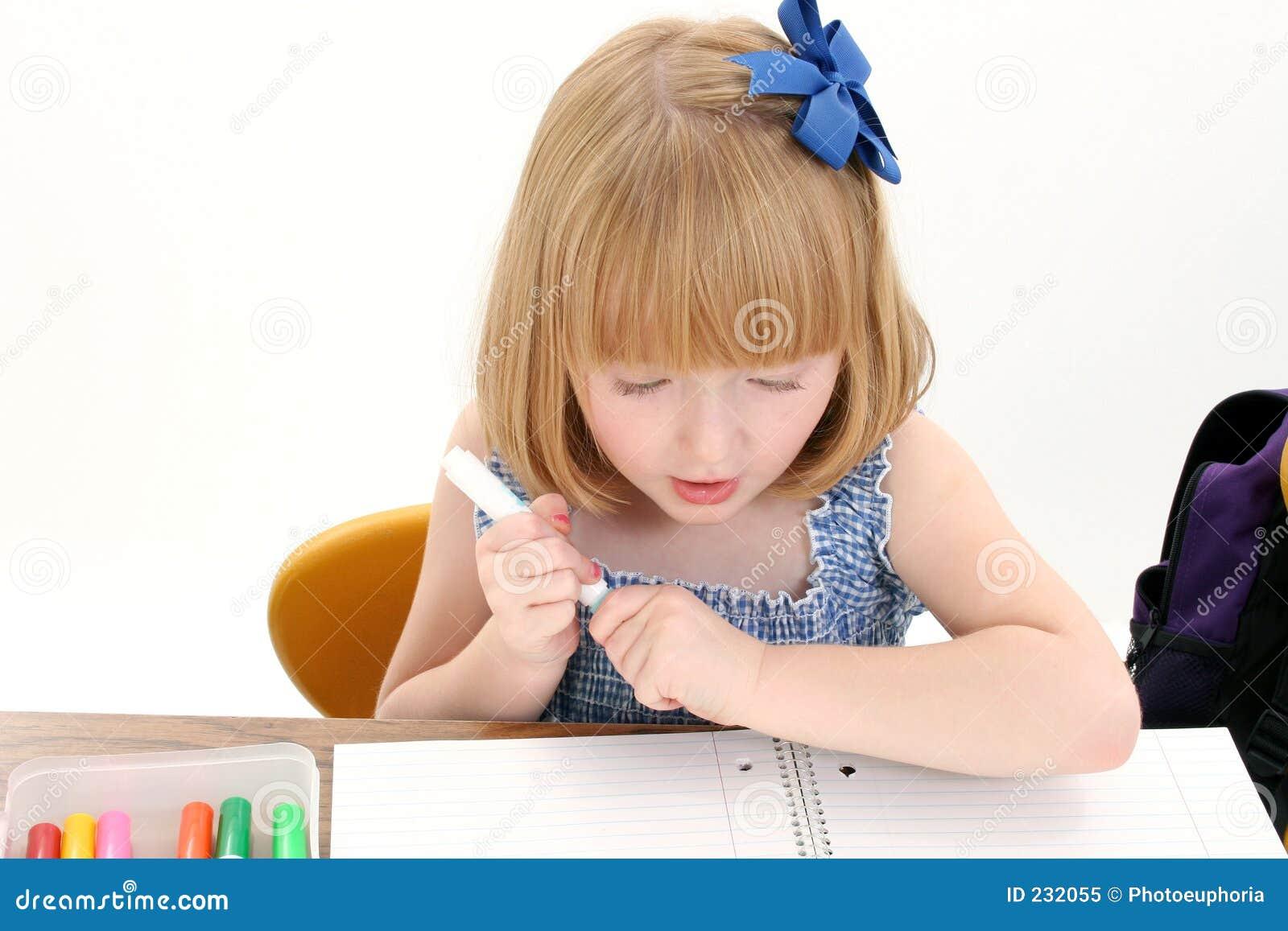 Schönes kleines Mädchen am Schreibtisch mit Kasten der Markierungen und des Notizbuches