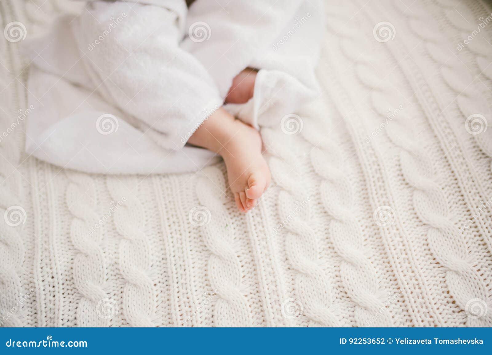 Schönes lächelndes neugeborenes Baby bedeckt mit weißem Bambustuch mit den Spaßohren Auf einem weißen Knit sitzen, helles Inter-