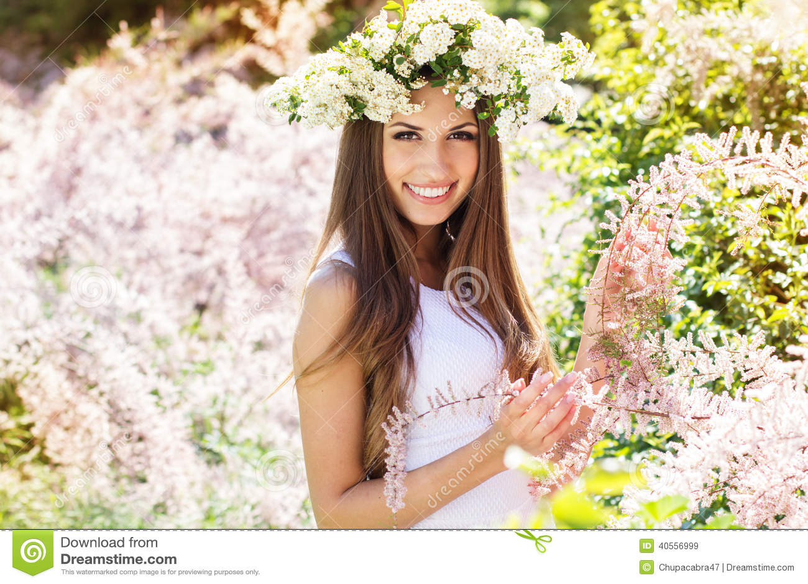 Schönes Mädchen auf der Natur im Kranz von Blumen