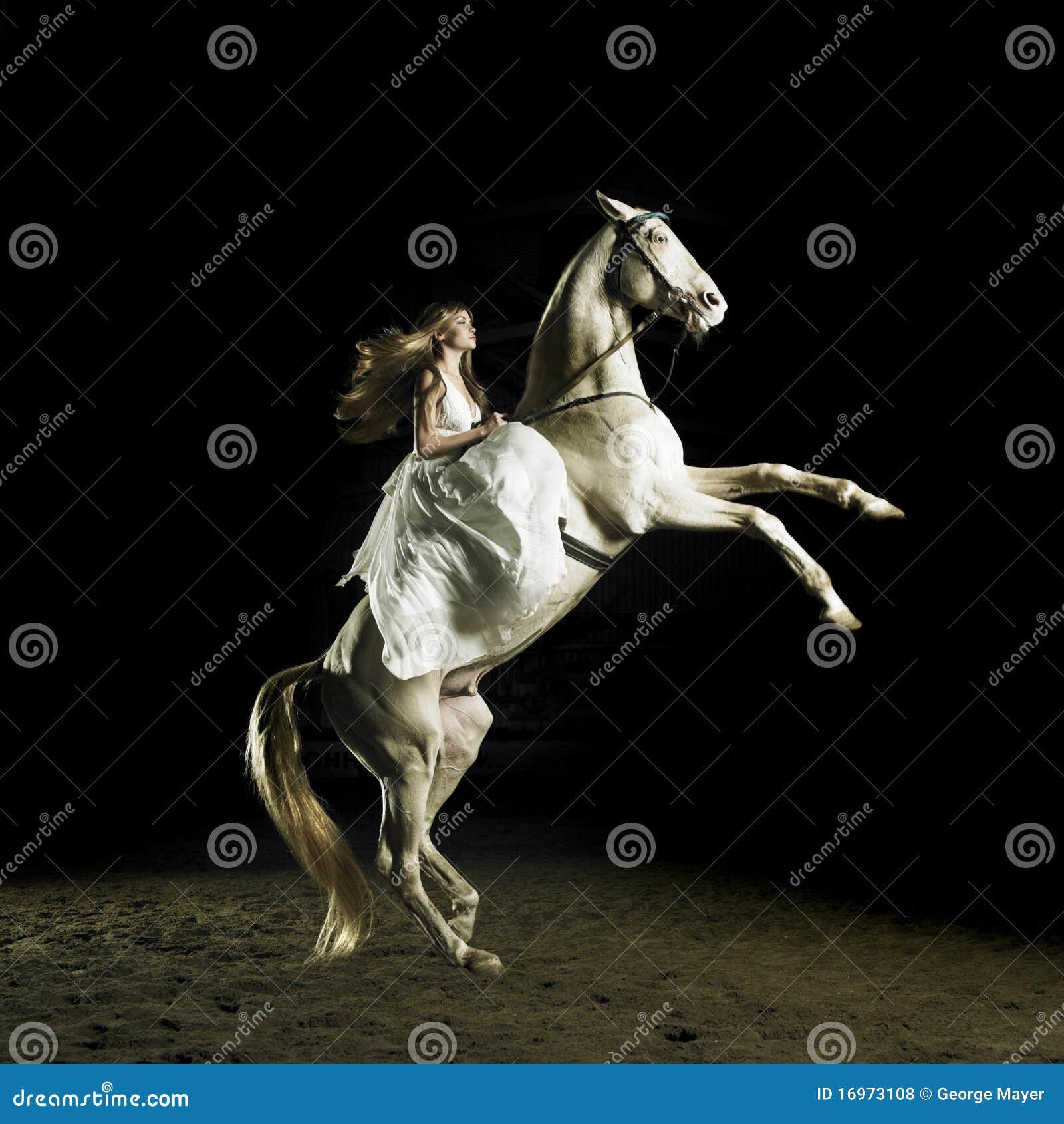 Schönes Mädchen auf einem weißen Pferd