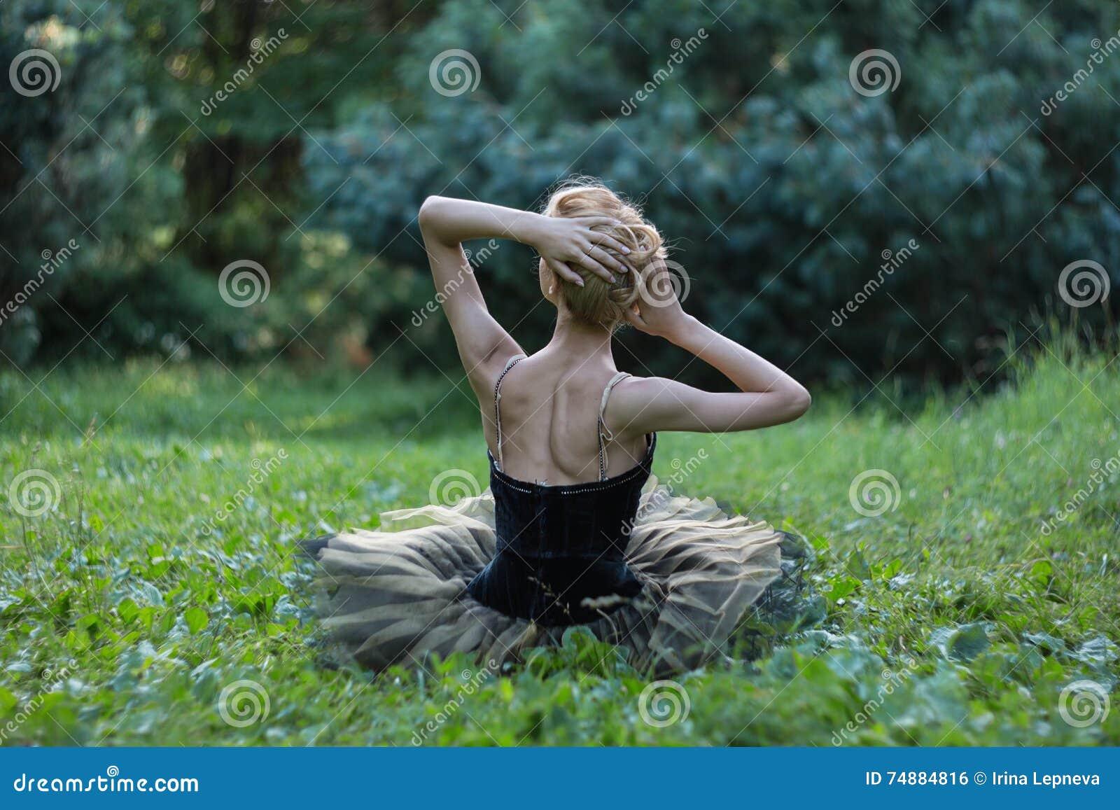 Schönes Mädchen, das auf einem Gras im Sommerpark liegt und stillsteht
